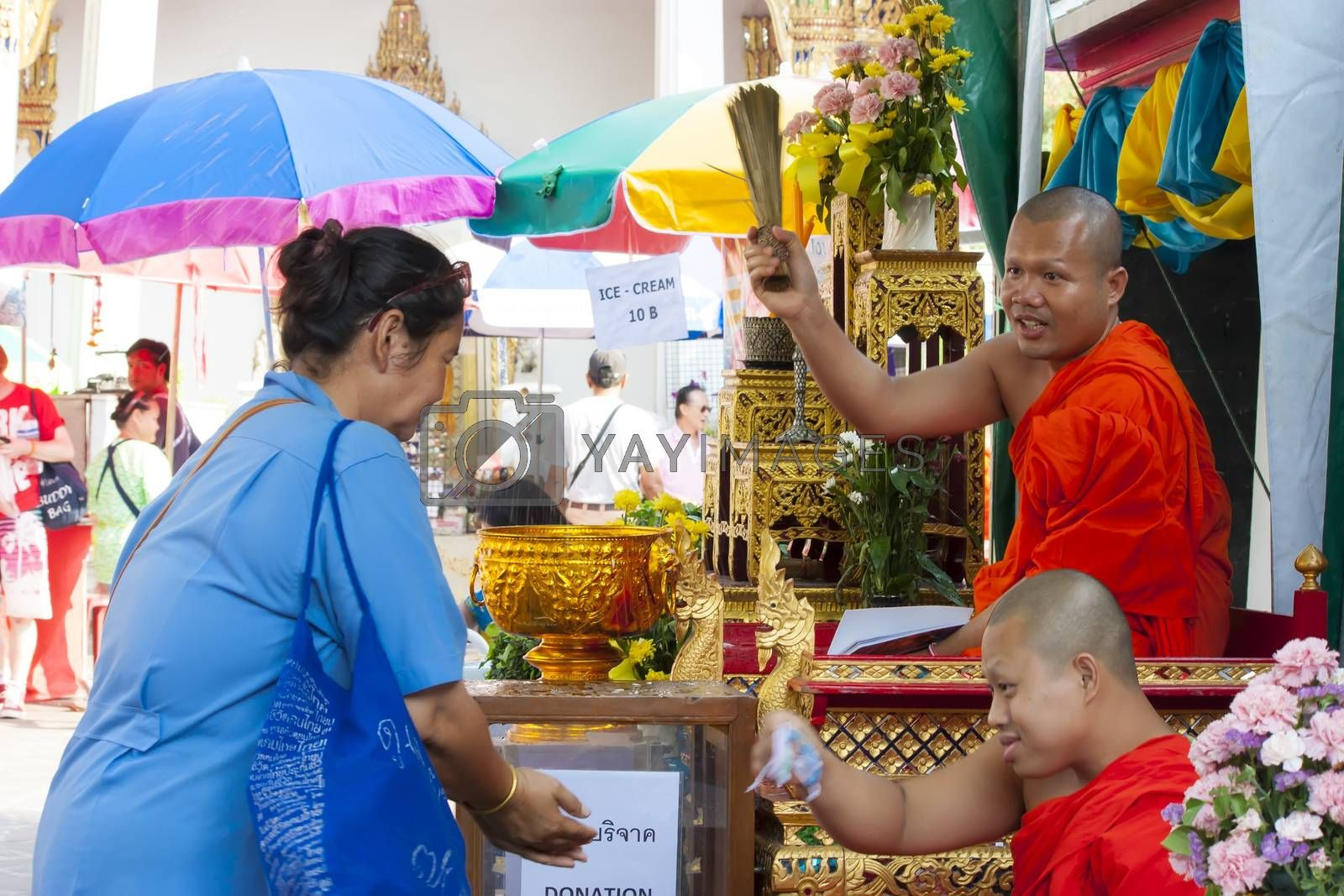 Unidentified monk pouring a holy water to people for a good luck in Songkran festival tradition of thailand. Photo: Amnarj2006/ yaymicro.com