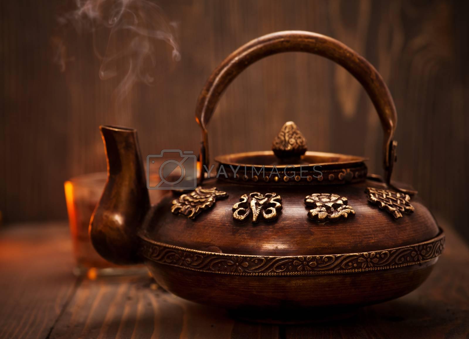 Antique iron hot tea pot fuming on dark wooden background
