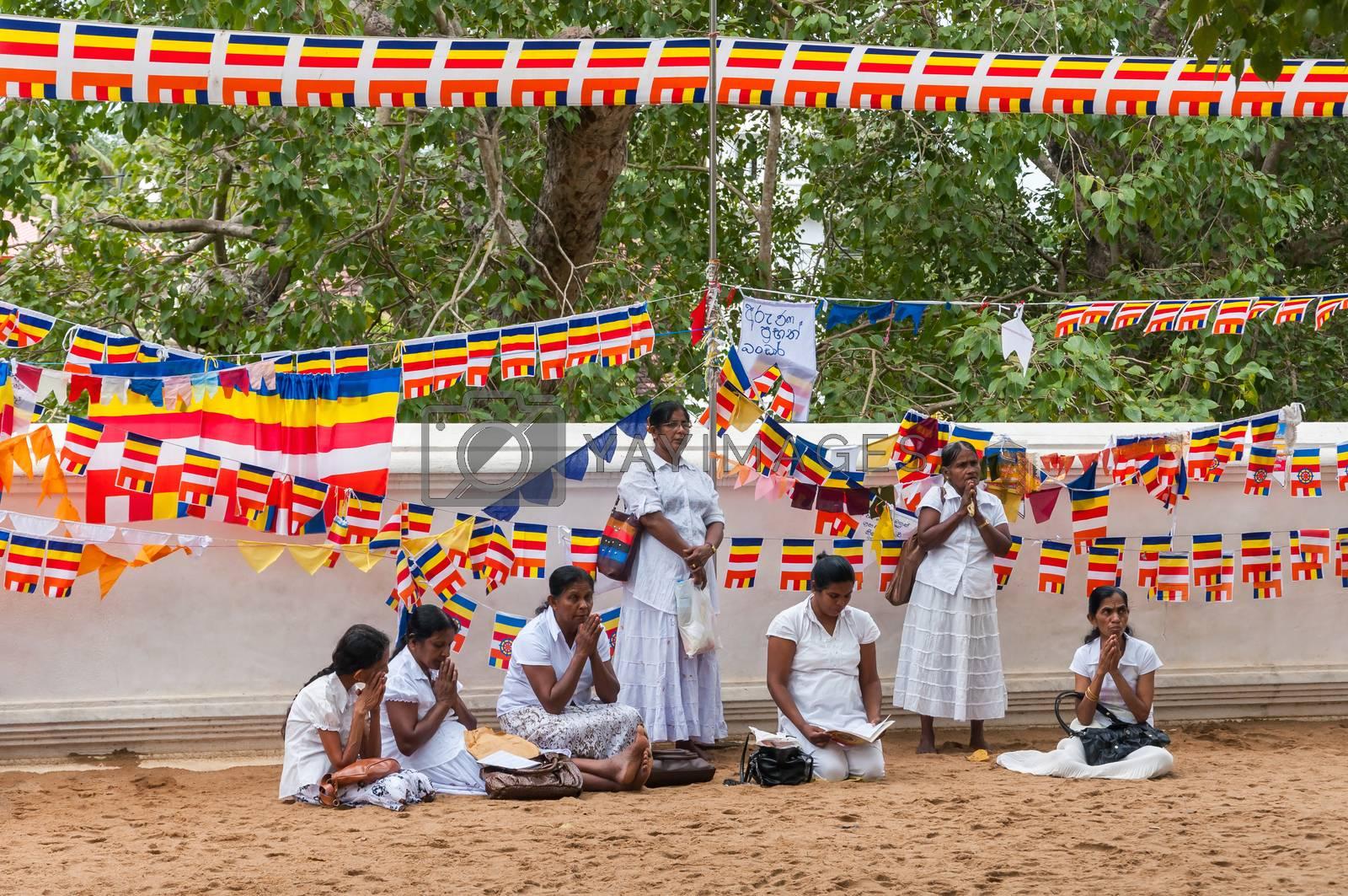 ANURADHAPURA, SRI LANKA - FEBRUARY 14: Sri Lankan women pray at buddhist temple on February 14, 2013 in Anuradhapura. The temple is location of Sri Maha Bodhi the oldest living human planted tree in the world.