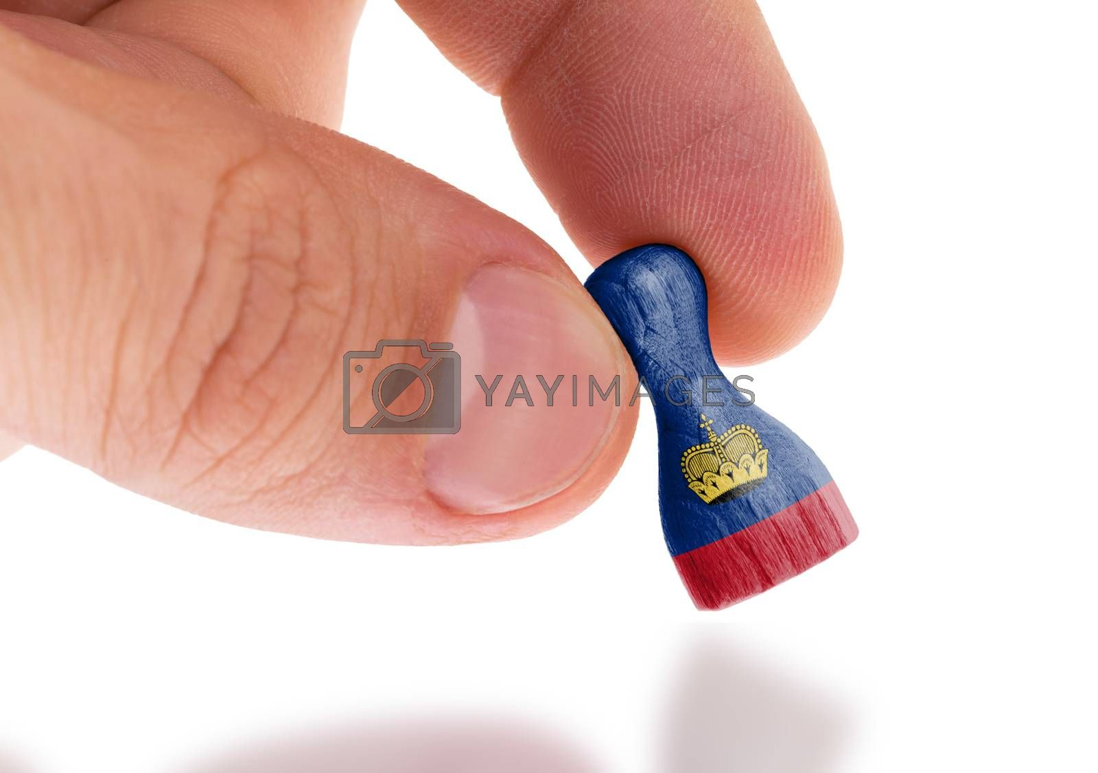 Hand holding wooden pawn, flag painting, selective focus by michaklootwijk