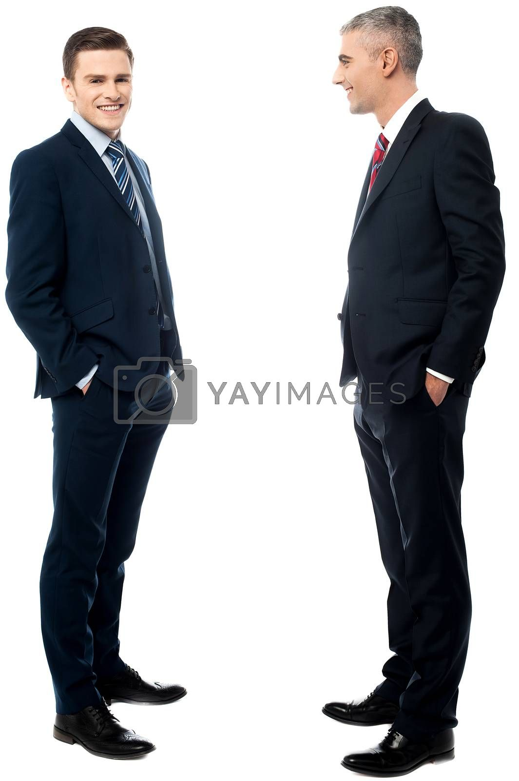 Businessmen posing with hands in pockets by stockyimages