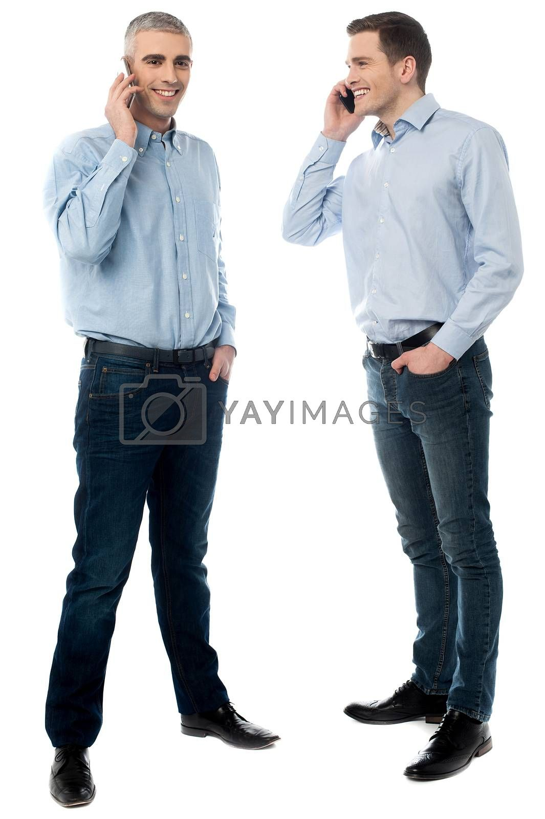 Two young men talking through mobile phone by stockyimages