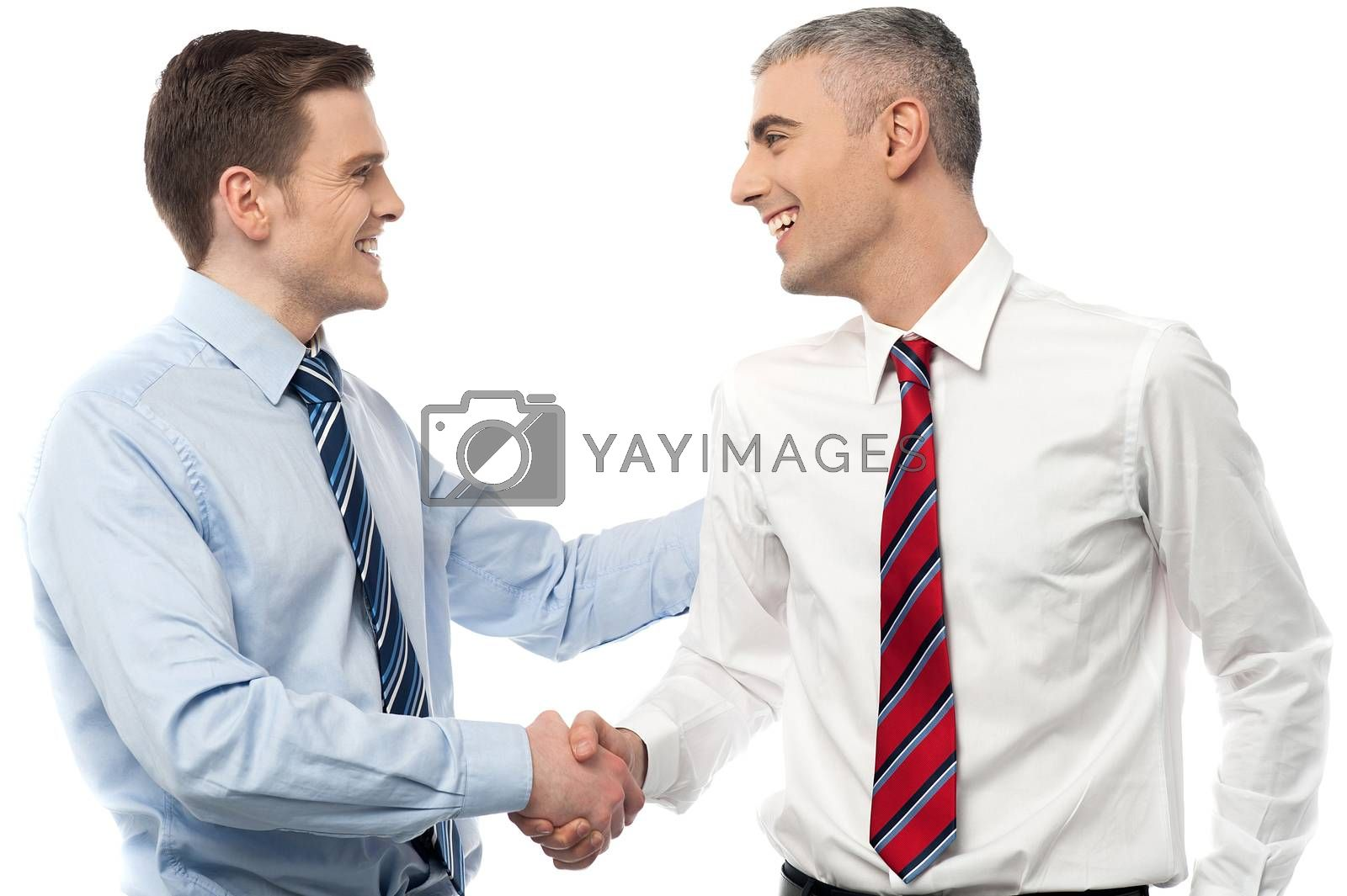 Smiling businessmen shaking hands by stockyimages