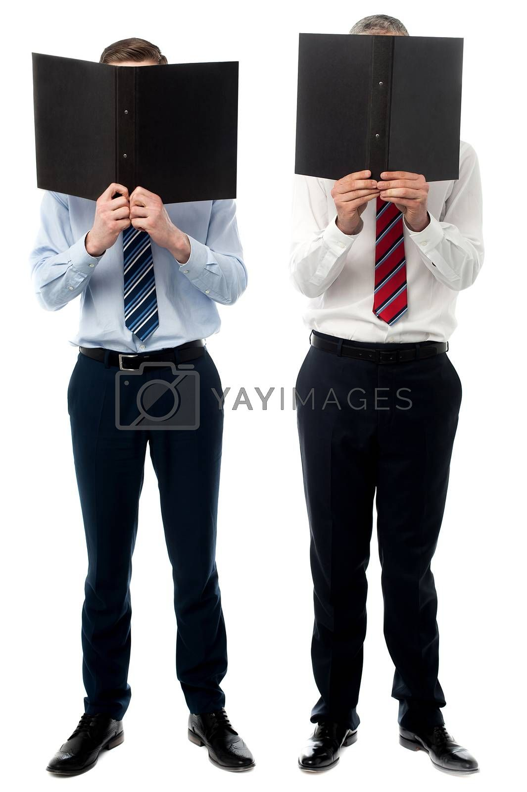 Businessmen hiding their faces with files by stockyimages