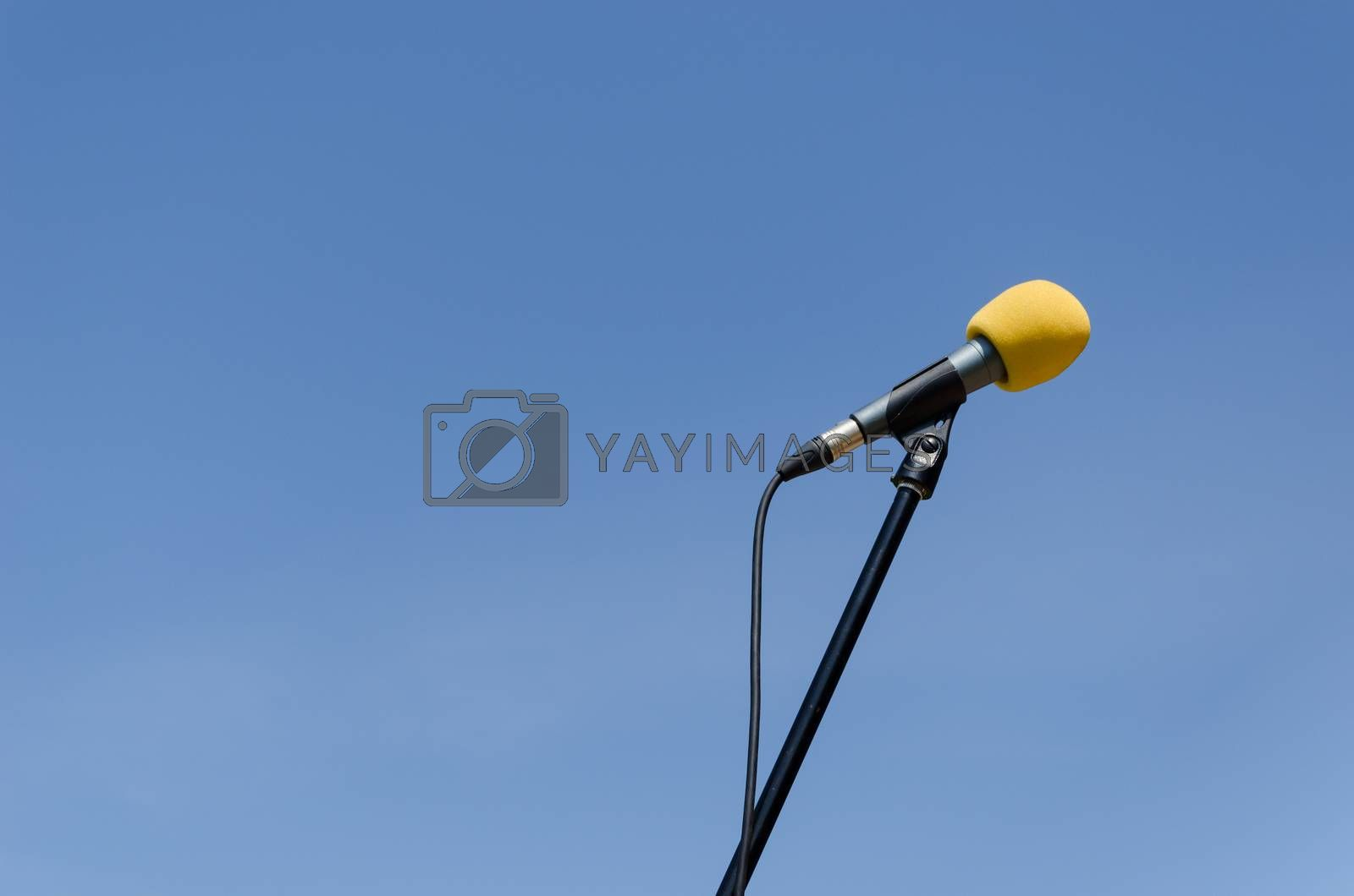 yellow microphone on blue sky background  by sauletas