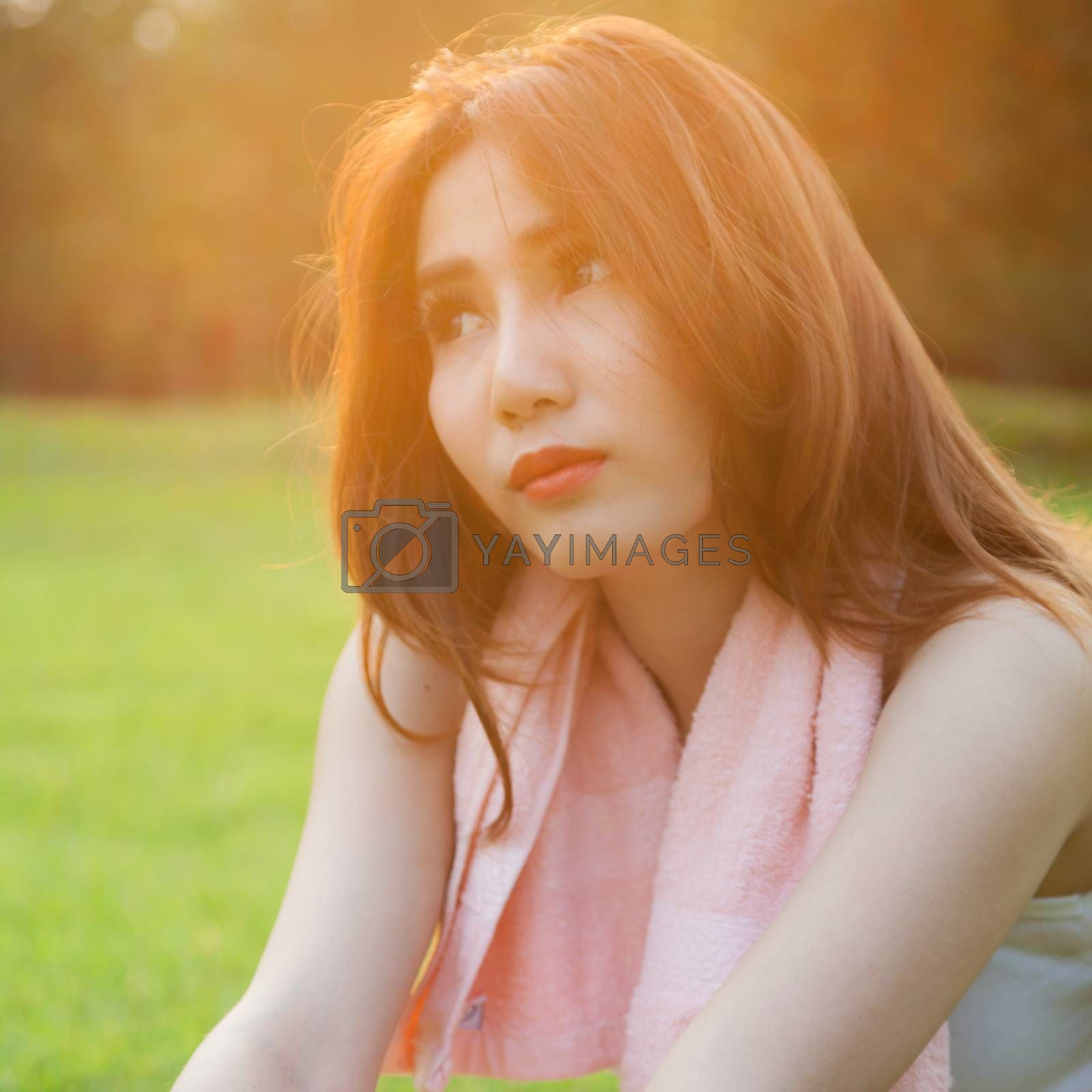 Woman sitting on lawn in park. by a454