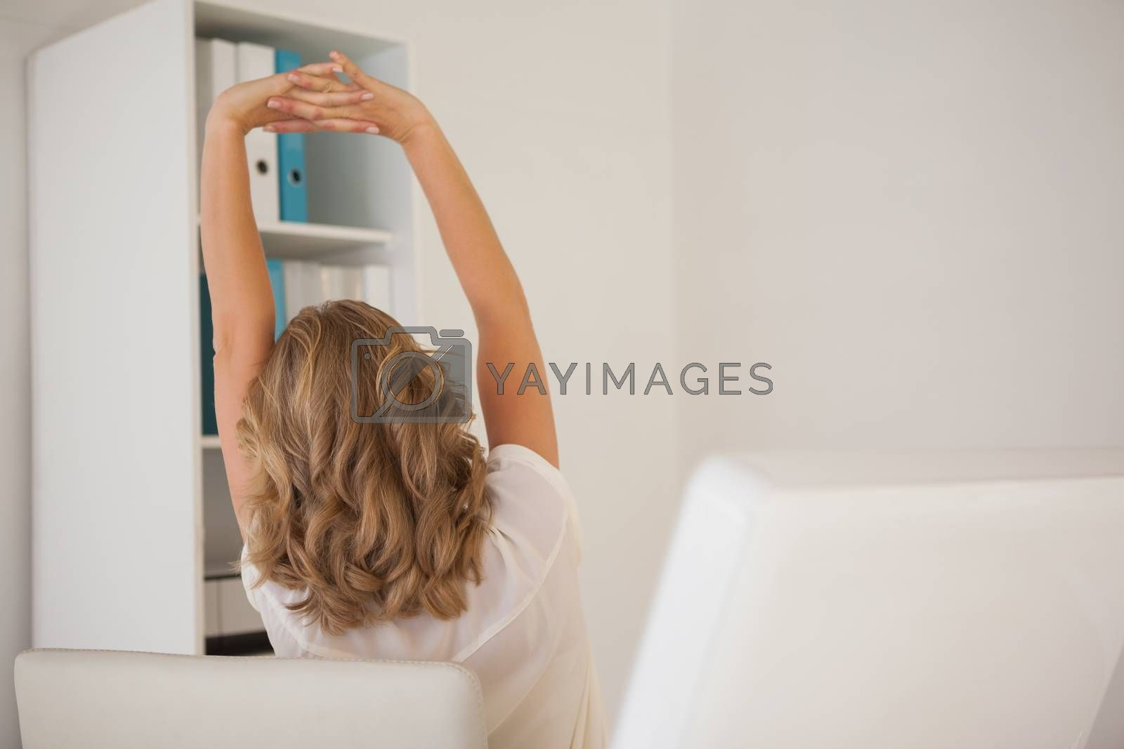 Royalty free image of Casual businesswoman stretching at her desk by Wavebreakmedia