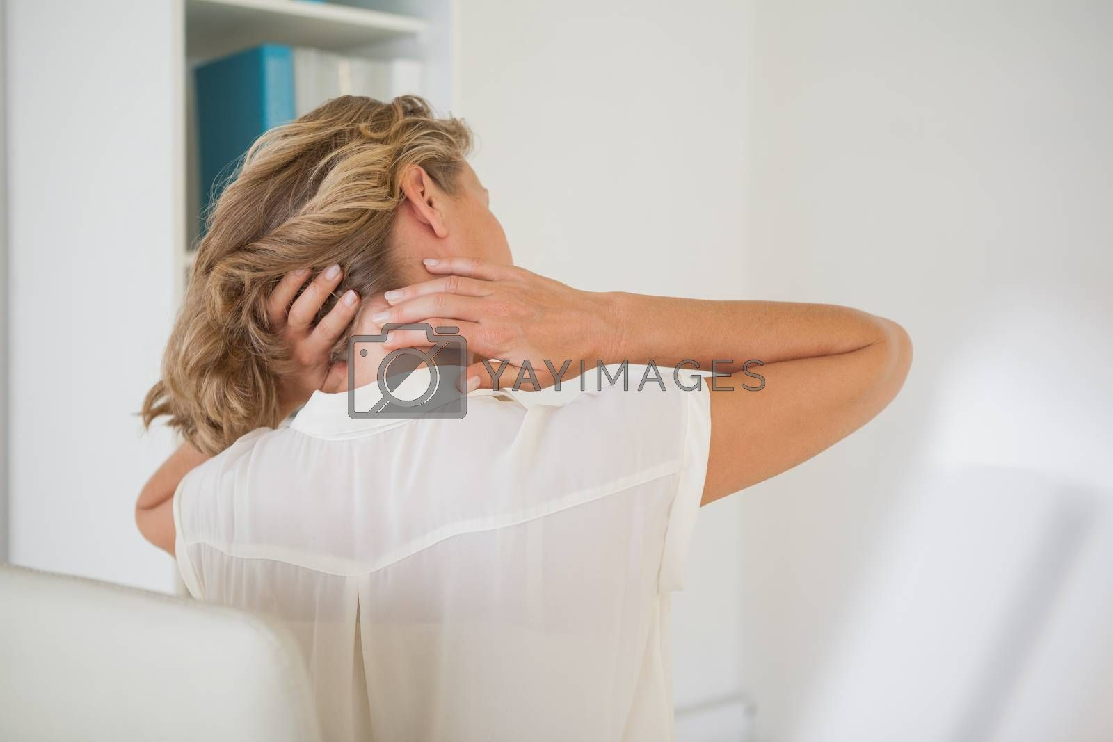 Royalty free image of Casual businesswoman rubbing her neck by Wavebreakmedia