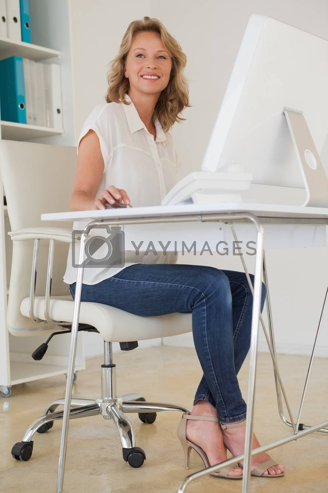 Royalty free image of Casual businesswoman smiling at her desk by Wavebreakmedia