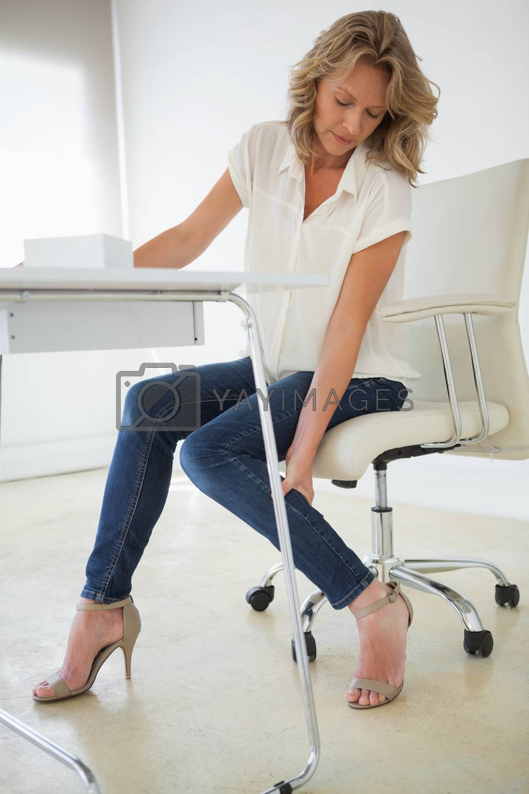 Royalty free image of Casual businesswoman touching her ankle by Wavebreakmedia