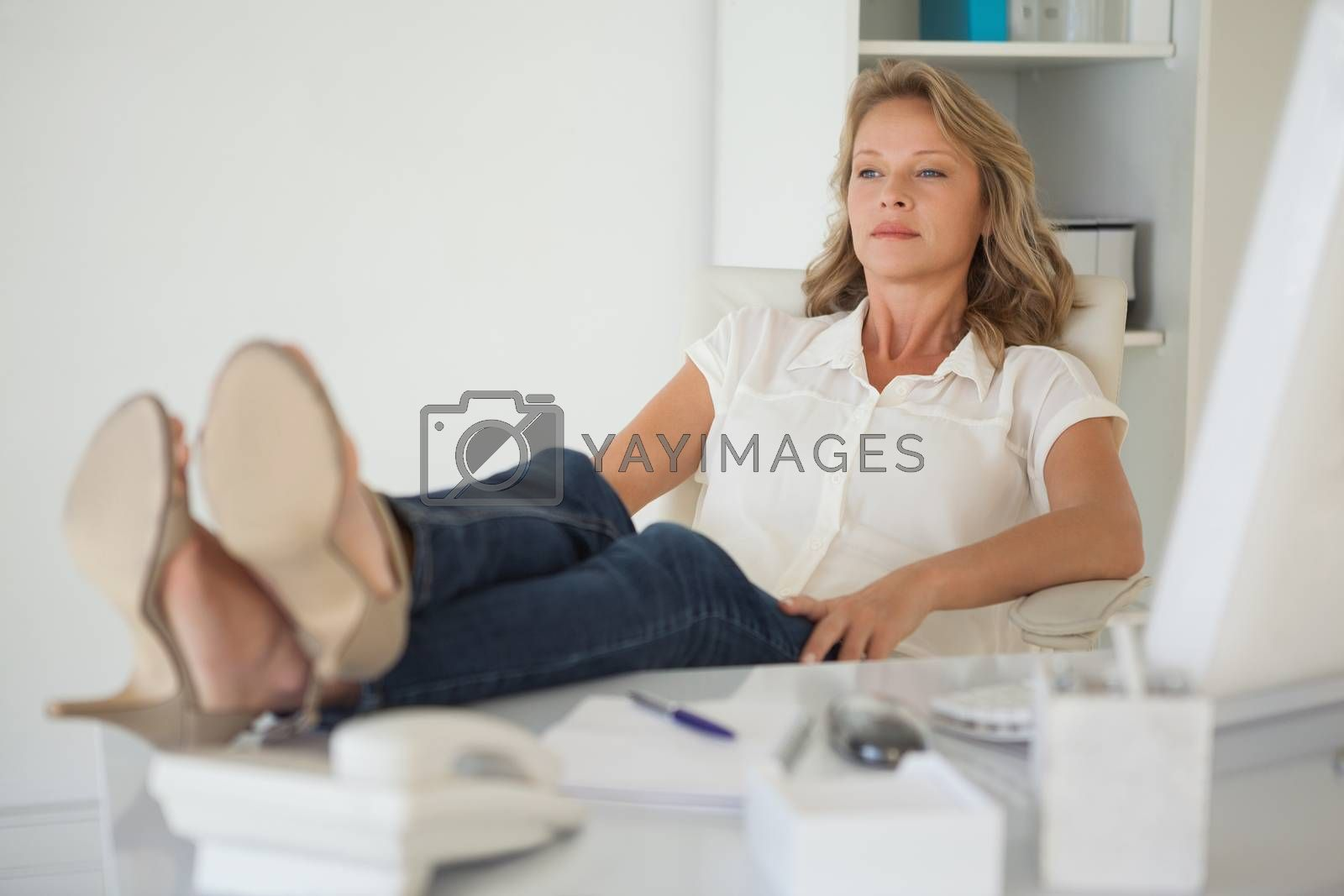 Royalty free image of Casual businesswoman sitting at her desk with feet up by Wavebreakmedia