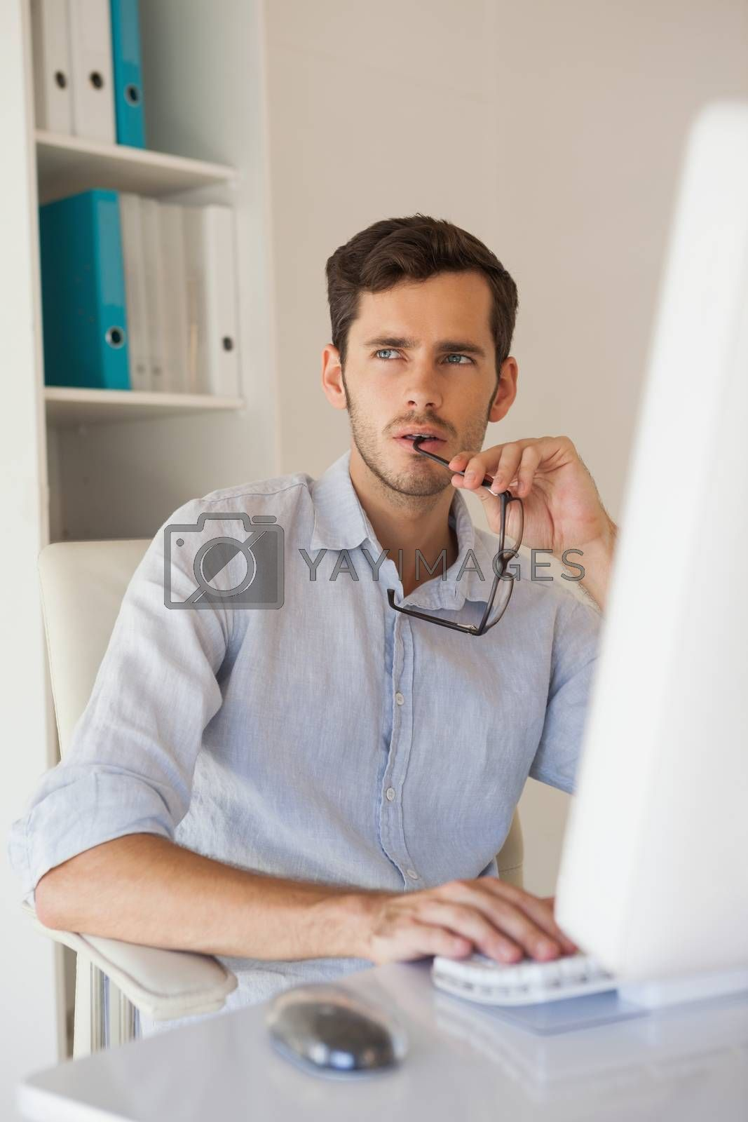 Royalty free image of Casual businessman thinking at his desk by Wavebreakmedia