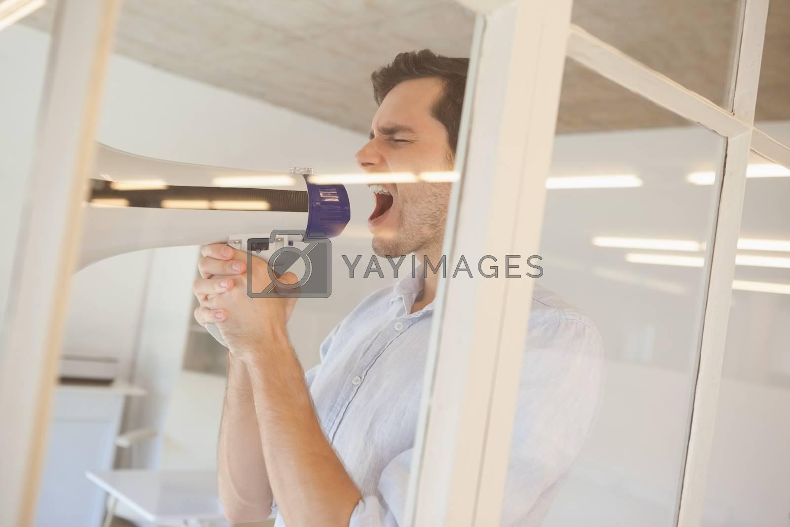 Royalty free image of Casual businessman shouting through megaphone by Wavebreakmedia