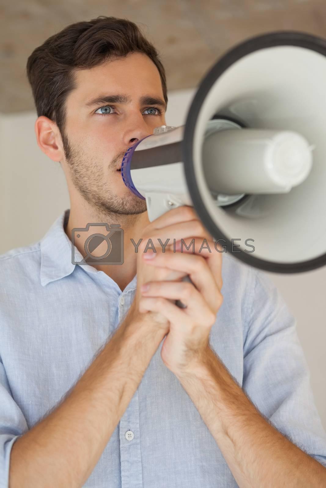 Royalty free image of Casual businessman talking through megaphone by Wavebreakmedia