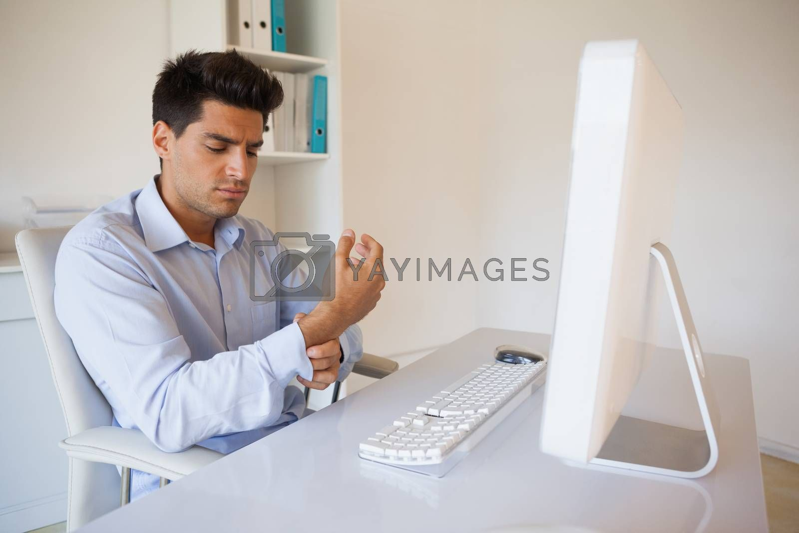 Royalty free image of Casual businessman touching his sore wrist by Wavebreakmedia