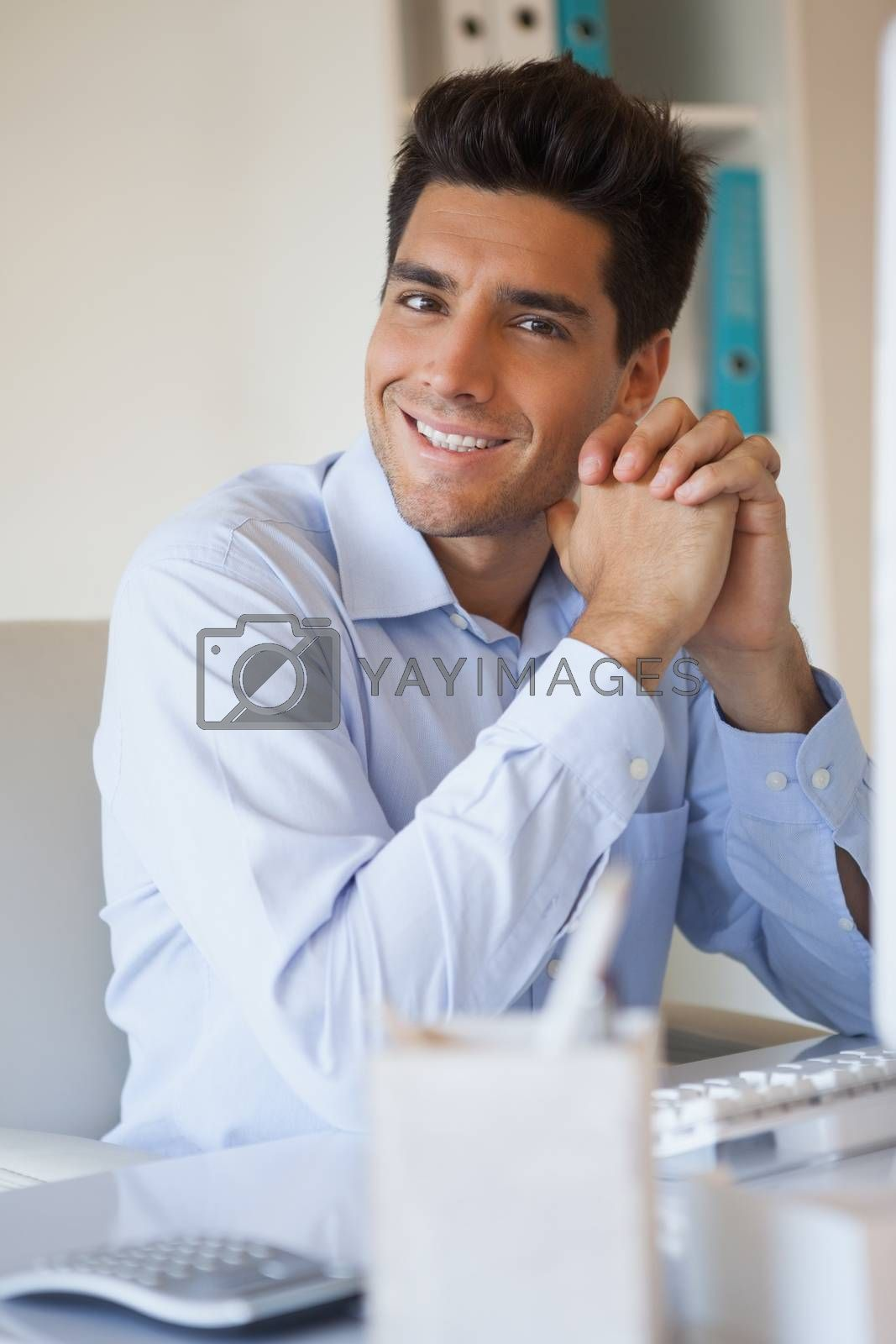Royalty free image of Casual businessman smiling at camera at his desk by Wavebreakmedia