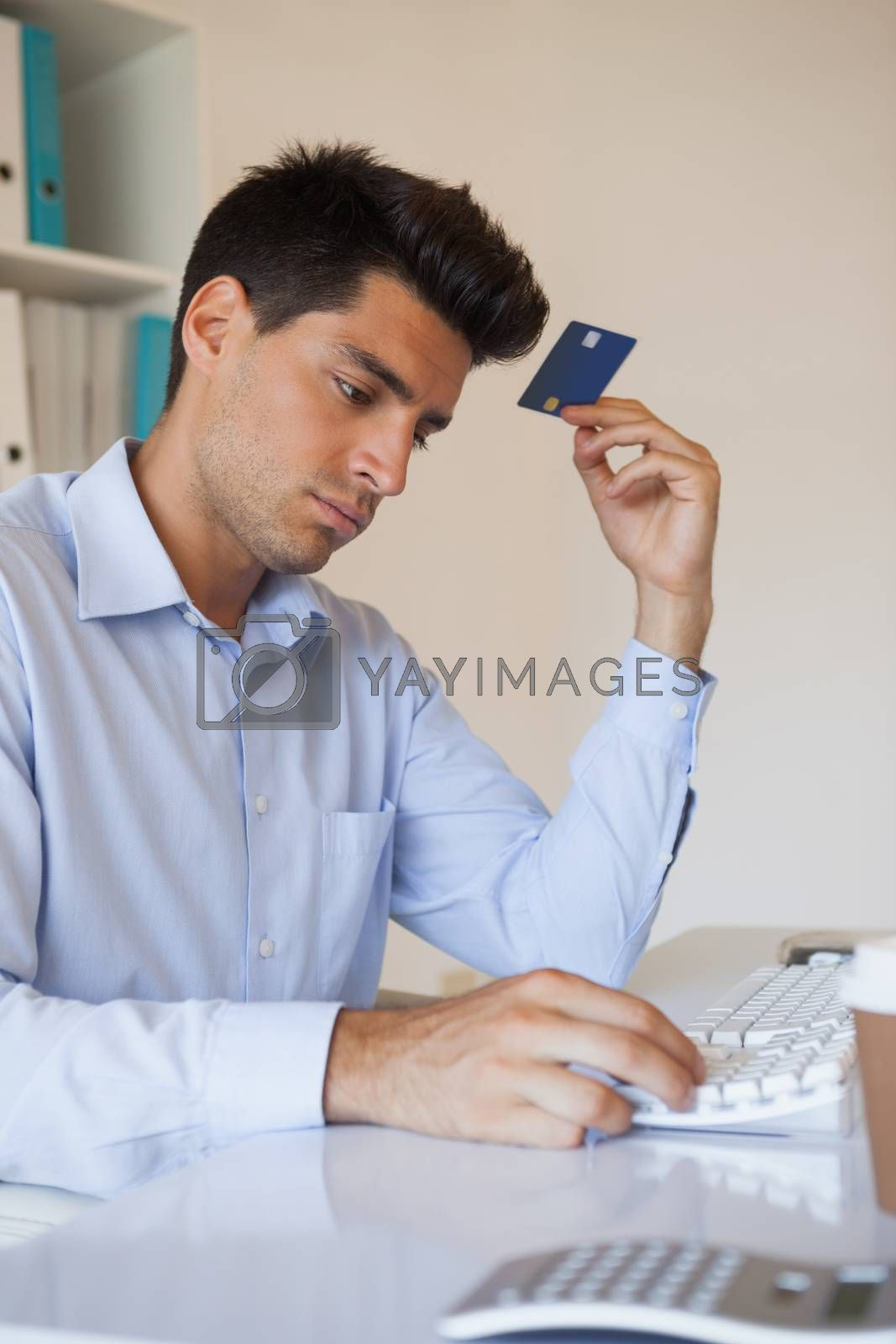 Royalty free image of Casual businessman shopping online at his desk by Wavebreakmedia