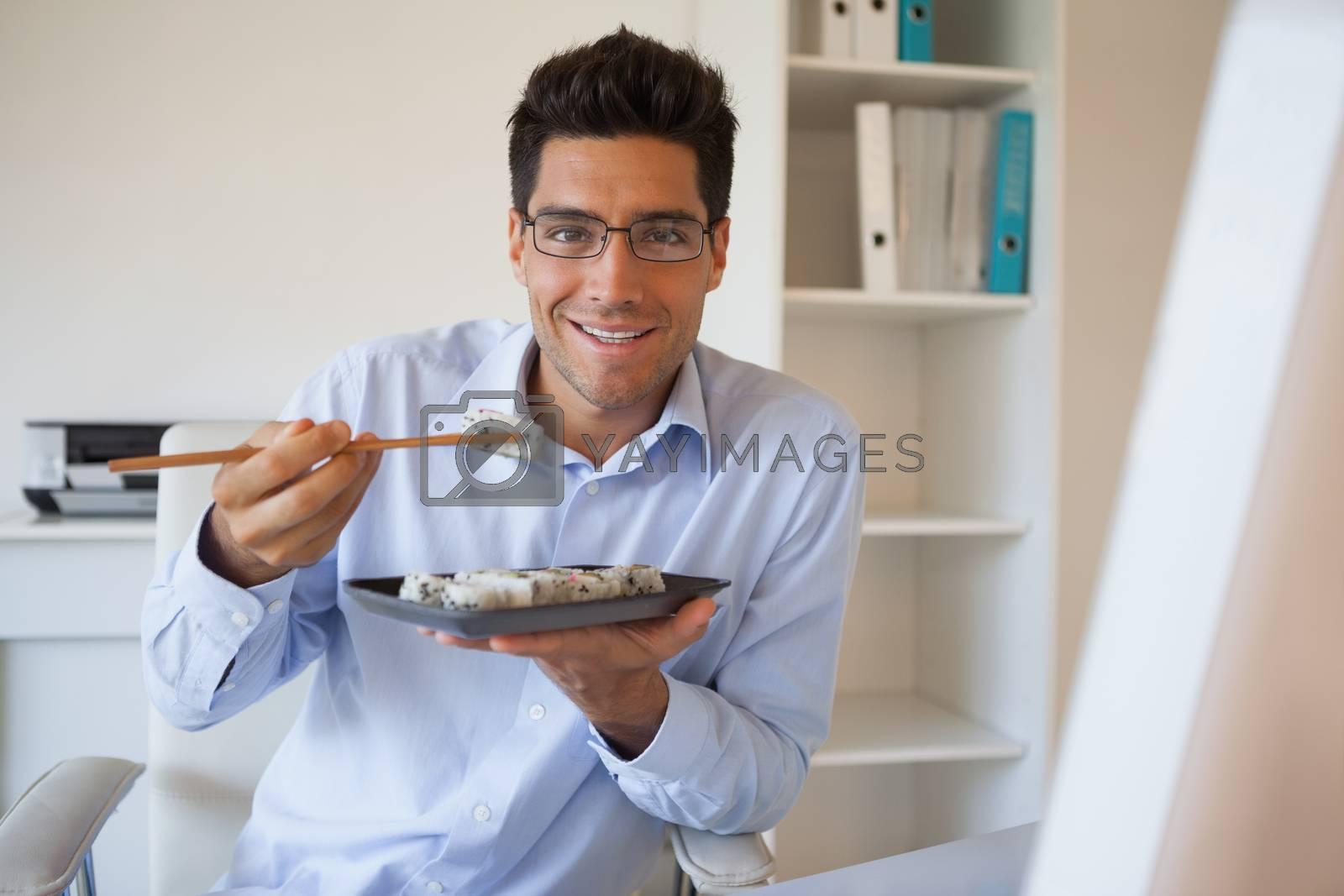 Royalty free image of Casual businessman enjoying sushi at his desk by Wavebreakmedia