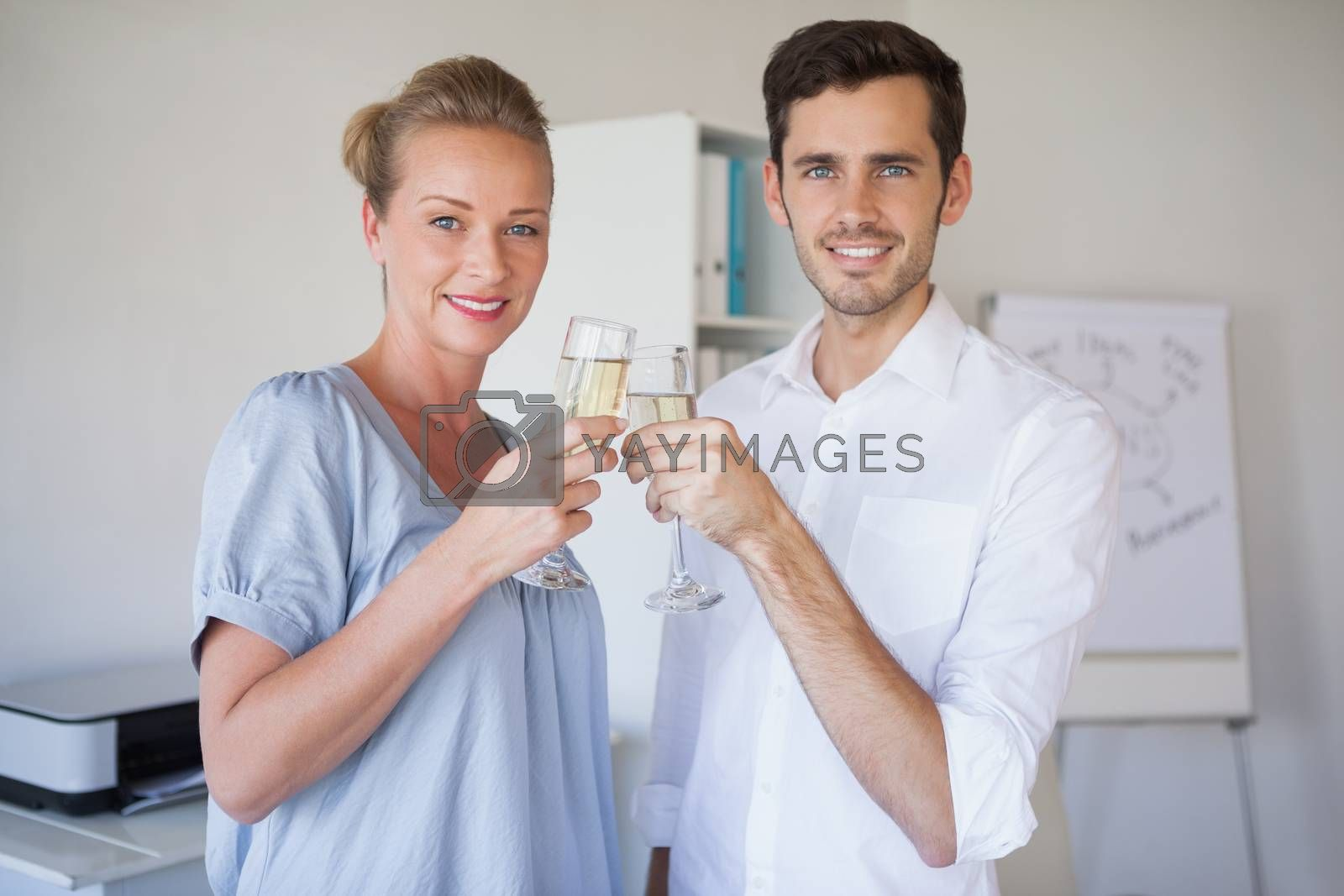 Royalty free image of Casual business team smiling at camera toasting with champagne by Wavebreakmedia
