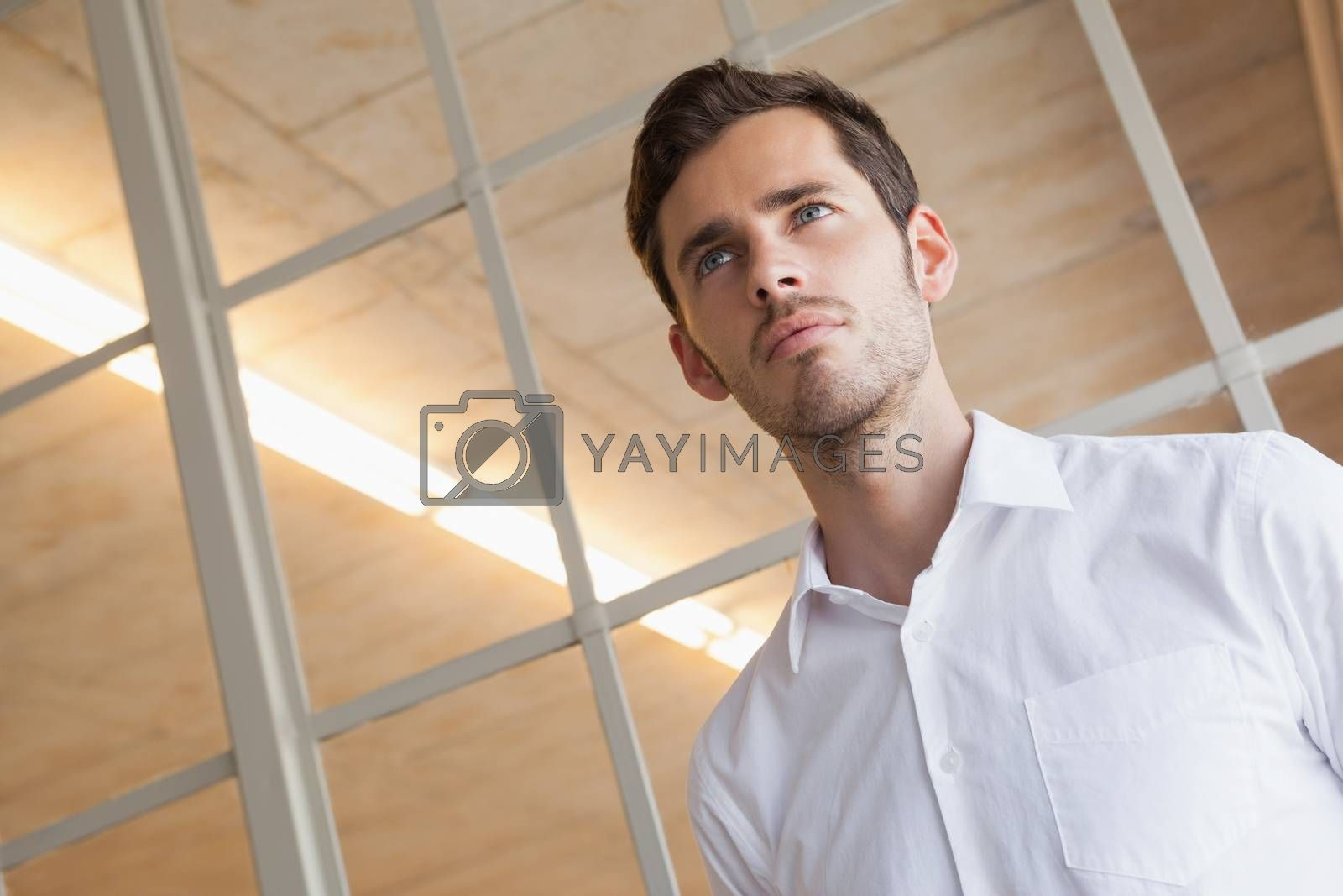 Royalty free image of Casual businessman standing with serious expression by Wavebreakmedia