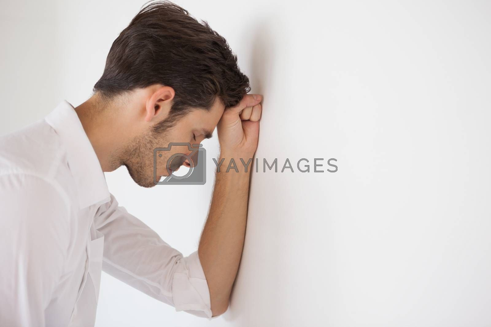 Royalty free image of Casual businessman leaning against the wall by Wavebreakmedia