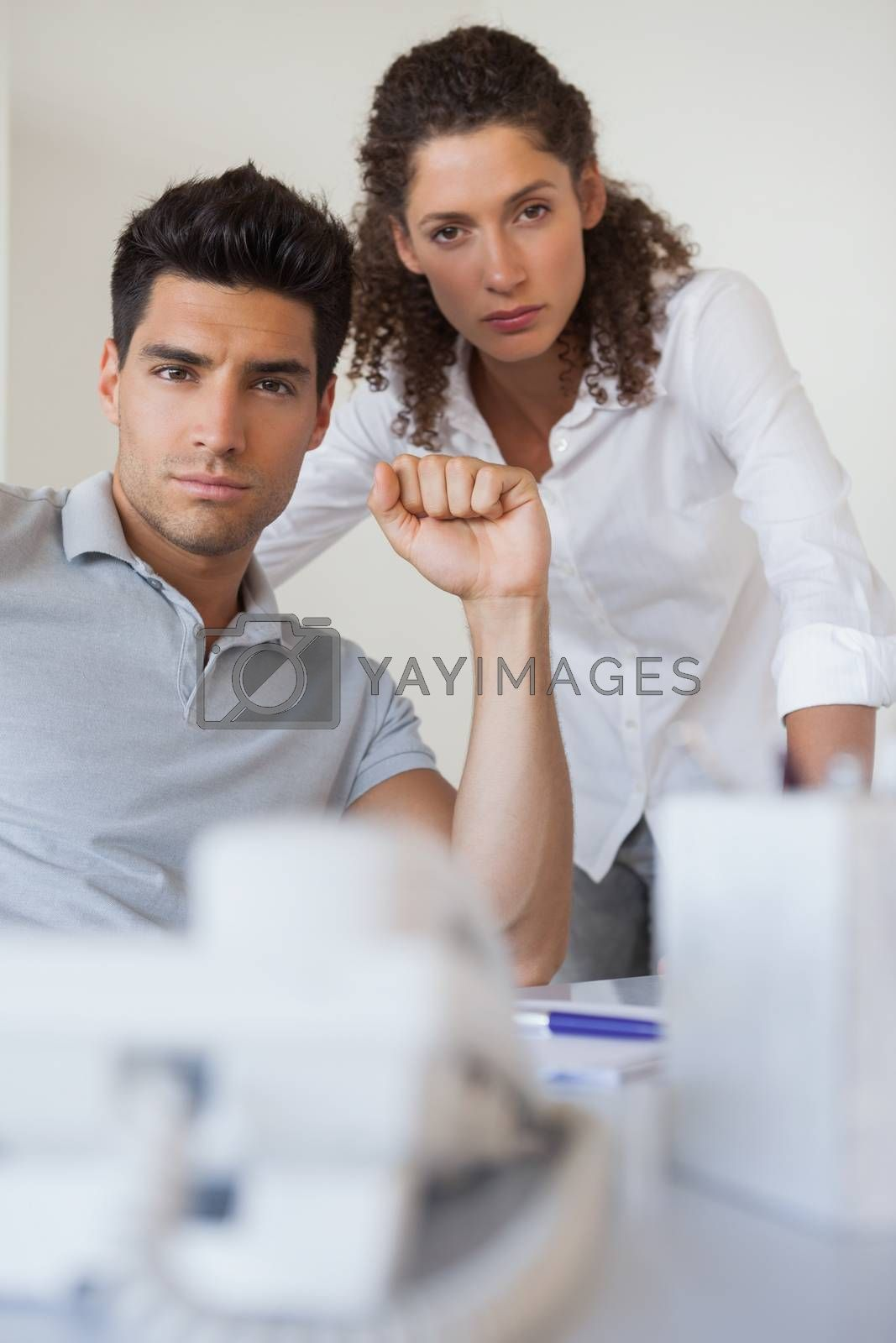 Royalty free image of Casual business team looking at camera together at desk by Wavebreakmedia
