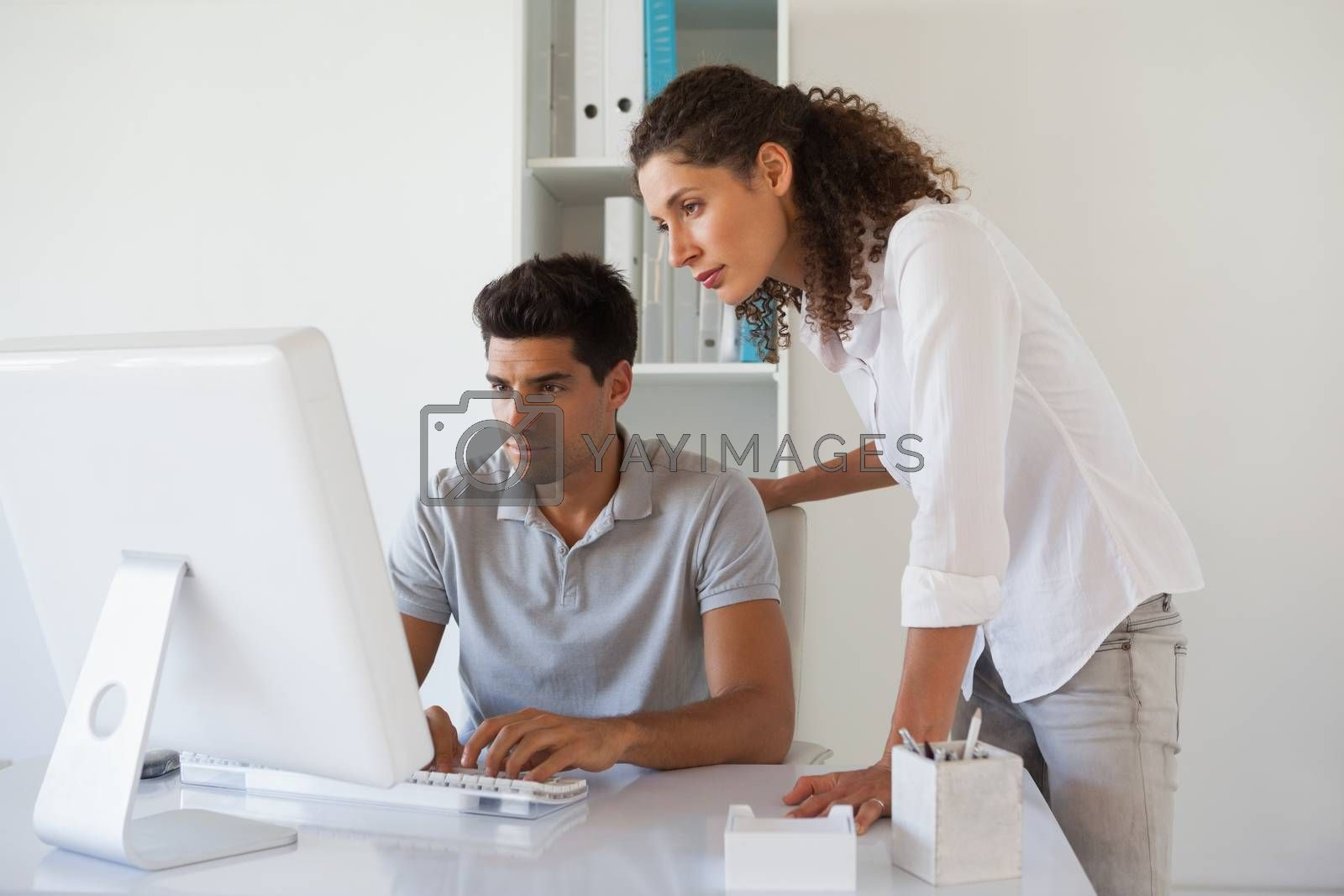 Royalty free image of Casual business team looking at computer together at desk by Wavebreakmedia