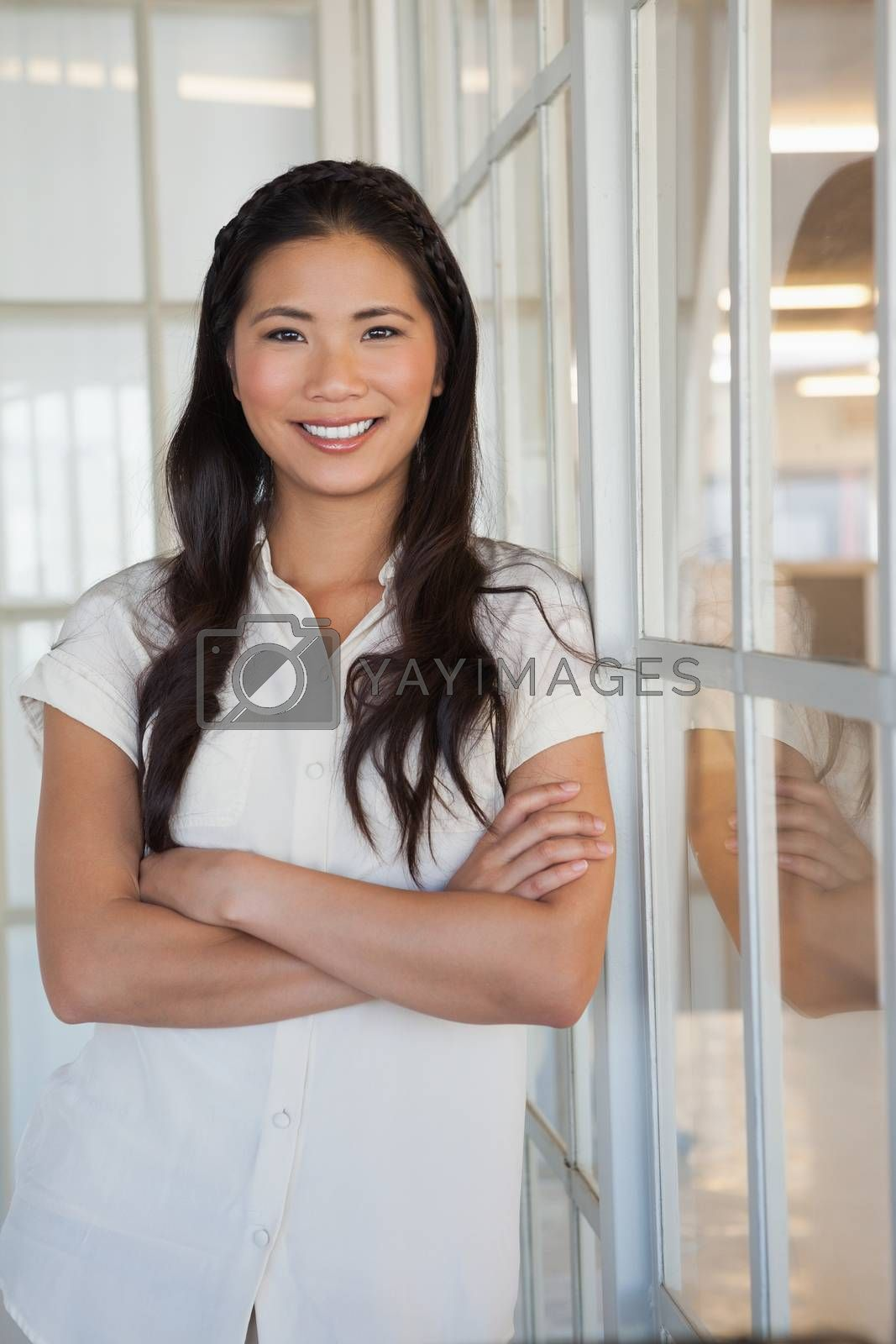 Royalty free image of Casual businesswoman smiling at camera with arms crossed by Wavebreakmedia