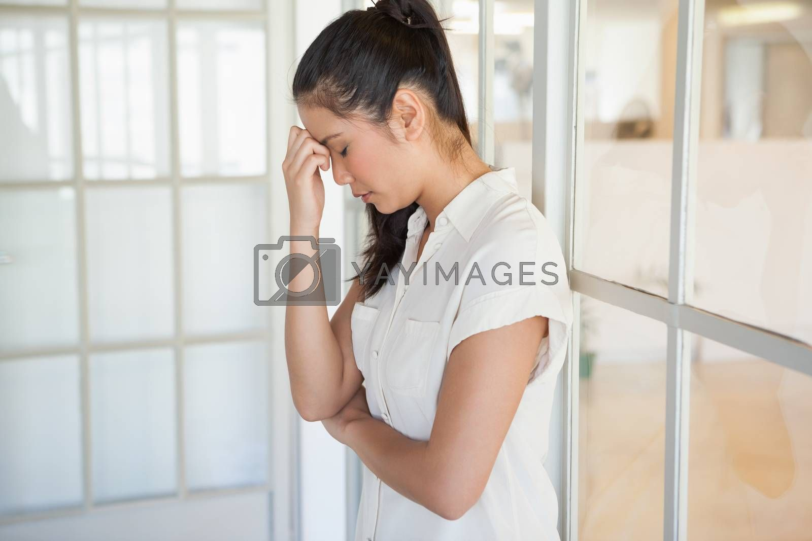 Royalty free image of Casual upset businesswoman with head bowed by Wavebreakmedia