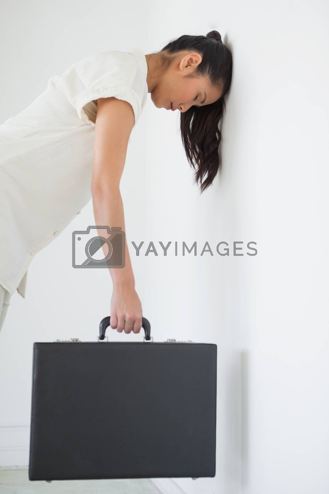 Royalty free image of Casual businesswoman leaning against wall with briefcase by Wavebreakmedia