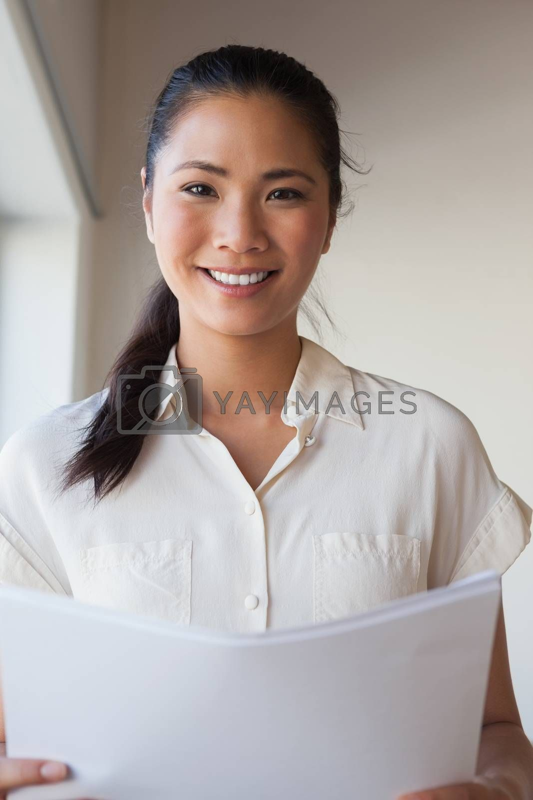 Royalty free image of Casual businesswoman holding document and smiling at camera by Wavebreakmedia