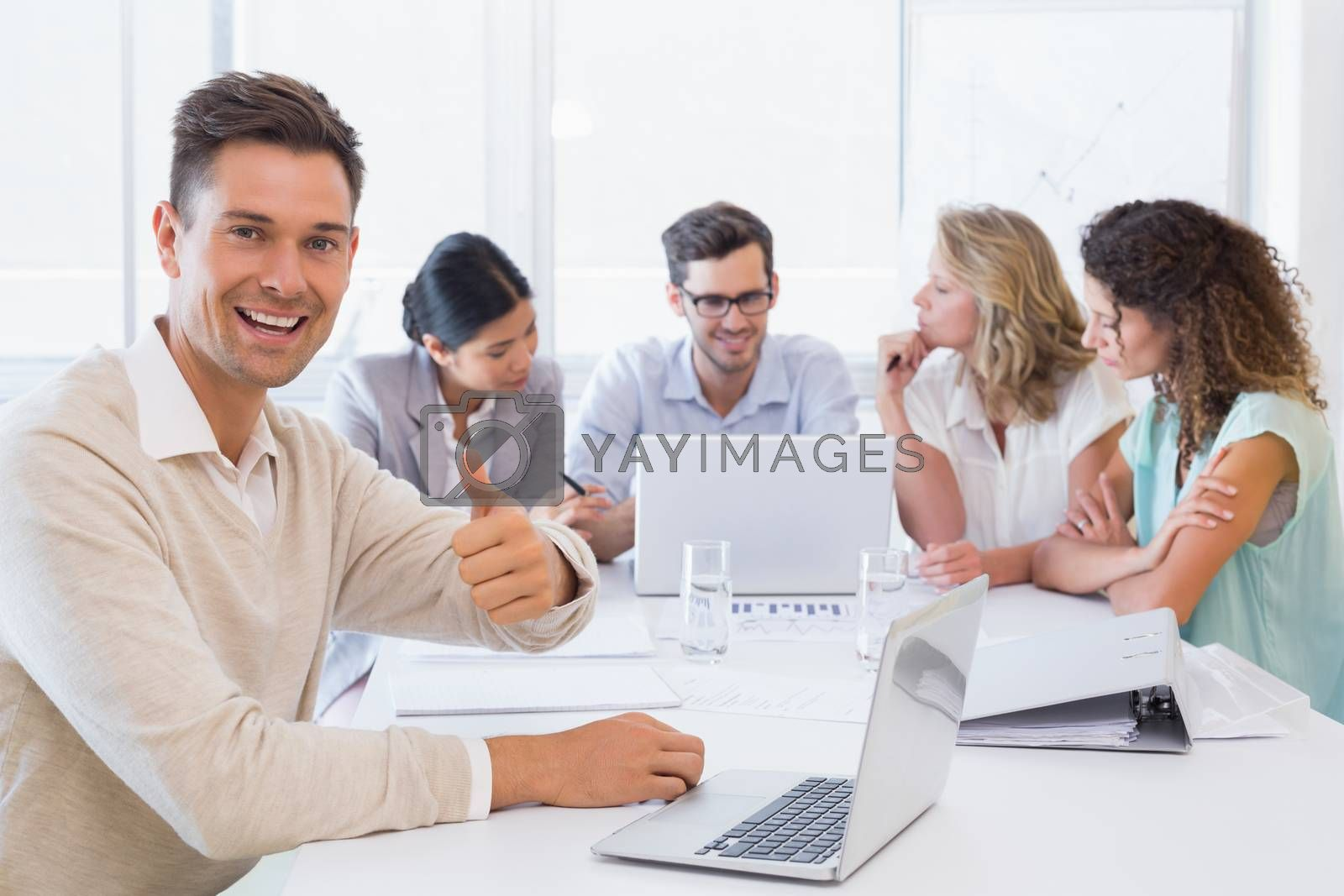 Royalty free image of Casual business team having a meeting with man giving thumbs up by Wavebreakmedia
