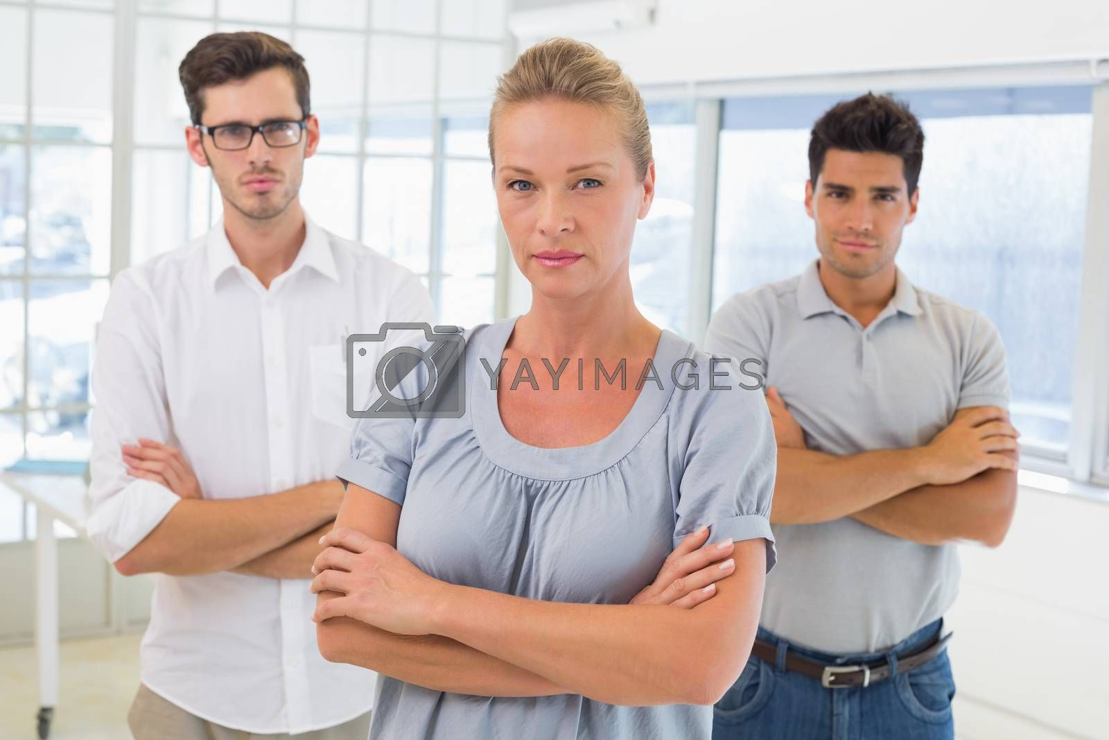 Royalty free image of Casual business team looking at camera with arms crossed by Wavebreakmedia