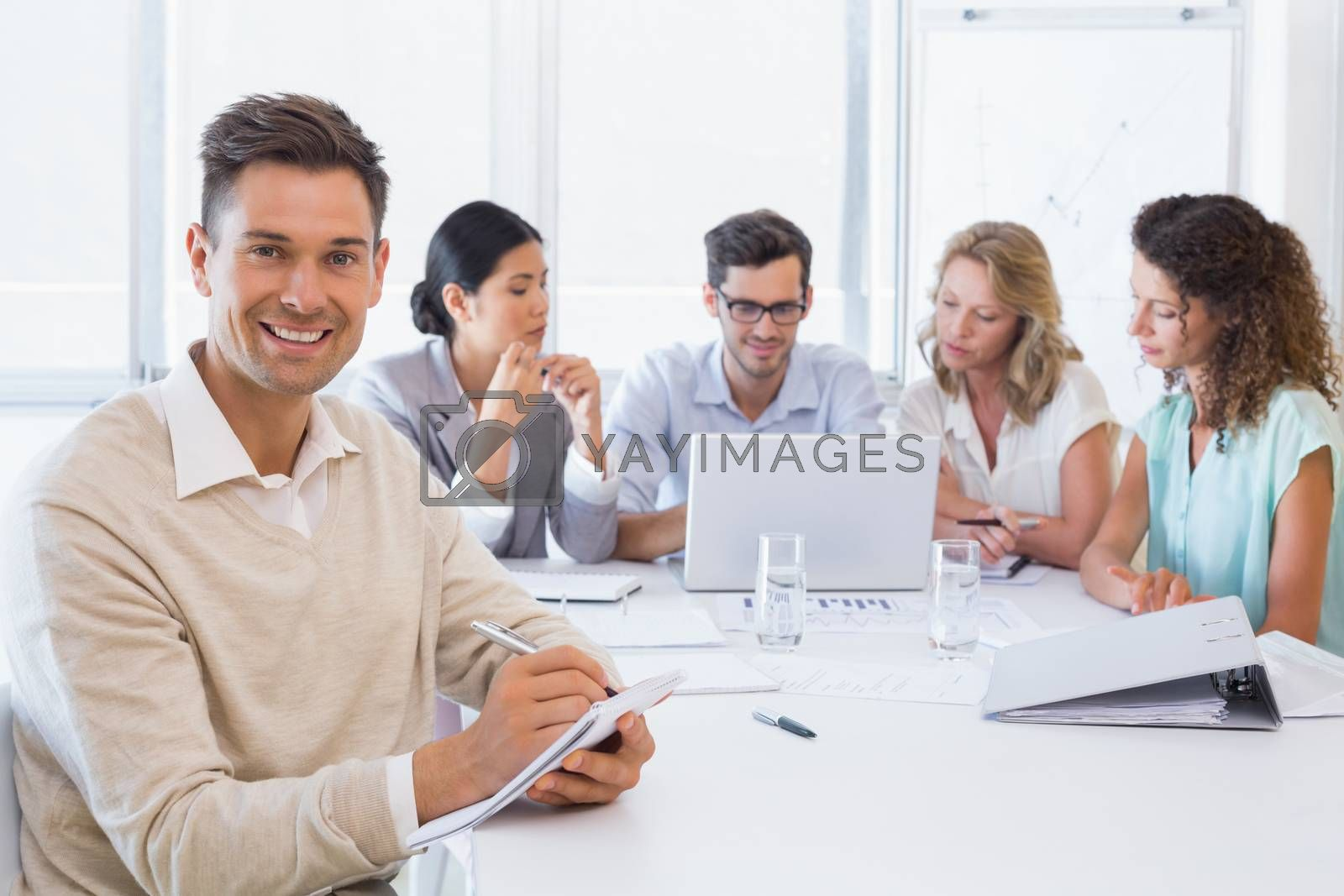 Royalty free image of Casual businessman taking notes during meeting by Wavebreakmedia