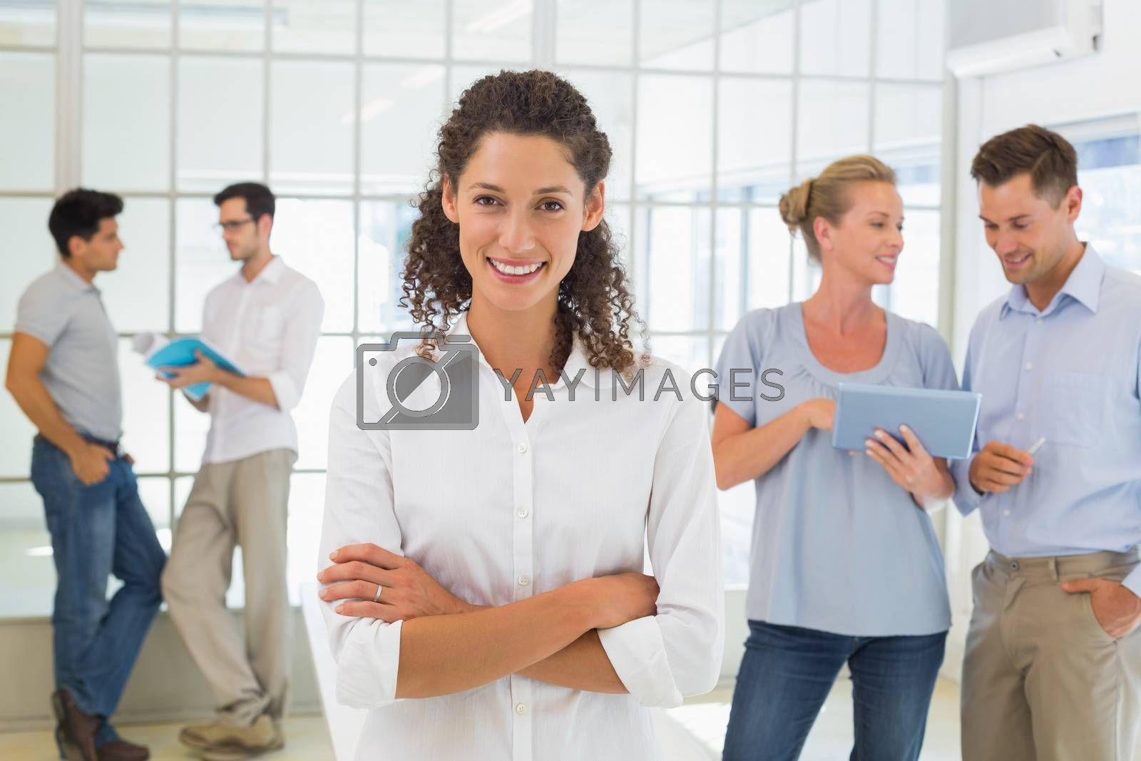 Royalty free image of Casual businesswoman smiling at camera with team behind her by Wavebreakmedia