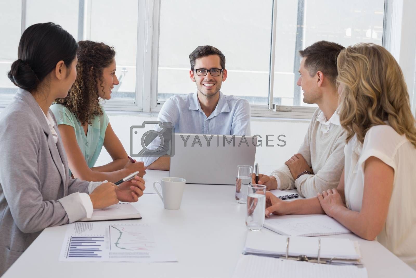Royalty free image of Casual boss smiling at camera dueing meeting with business team by Wavebreakmedia
