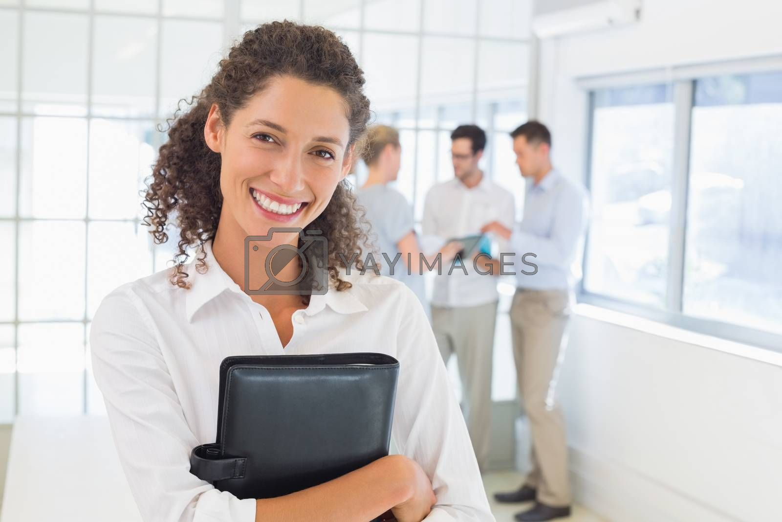 Royalty free image of Casual businesswoman smiling at camera holding diary by Wavebreakmedia