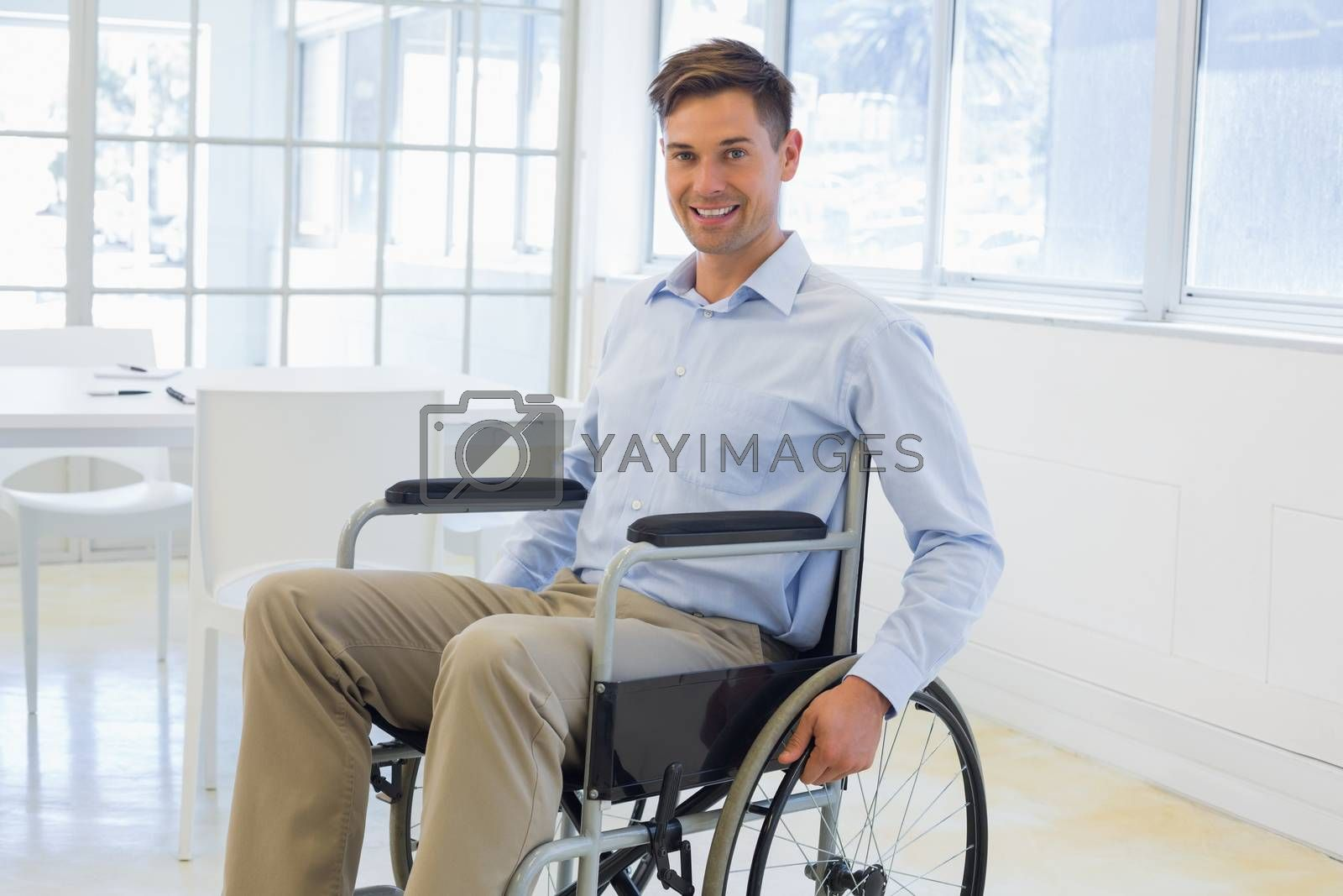 Royalty free image of Casual businessman in wheelchair smiling at camera by Wavebreakmedia