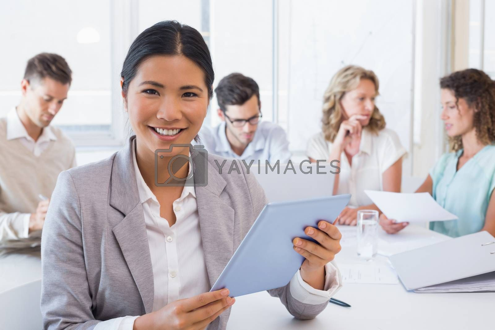 Royalty free image of Casual businesswoman using her tablet during a meeting by Wavebreakmedia
