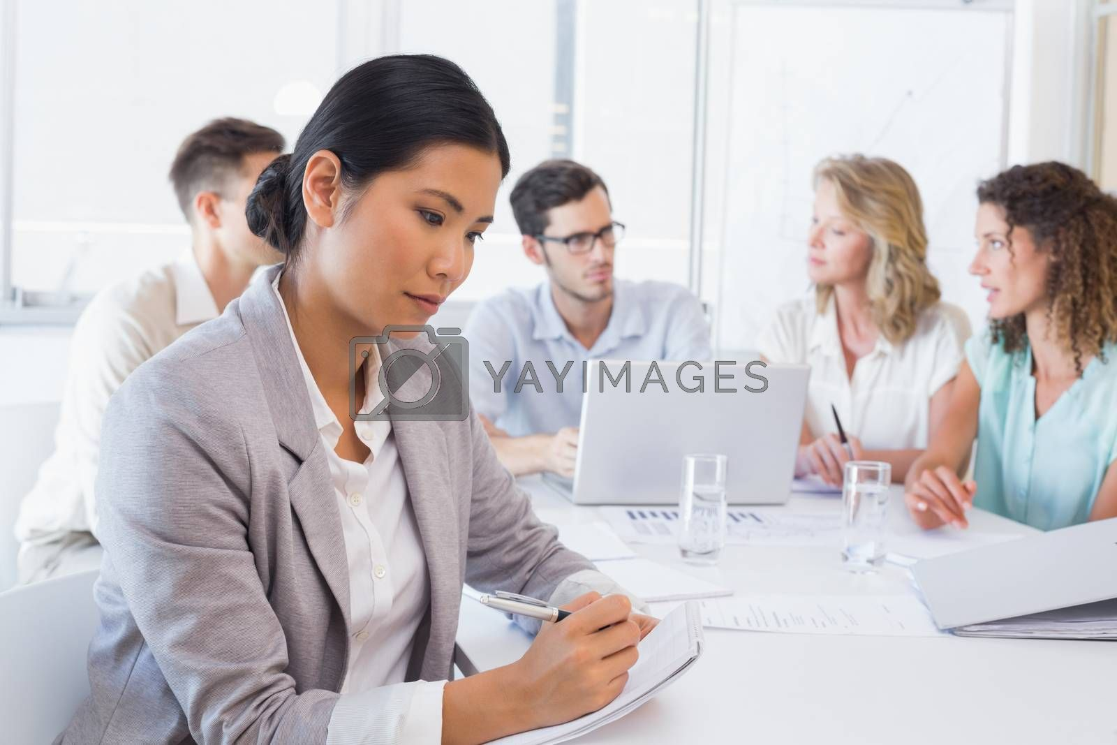 Royalty free image of Casual businesswoman taking notes during meeting by Wavebreakmedia