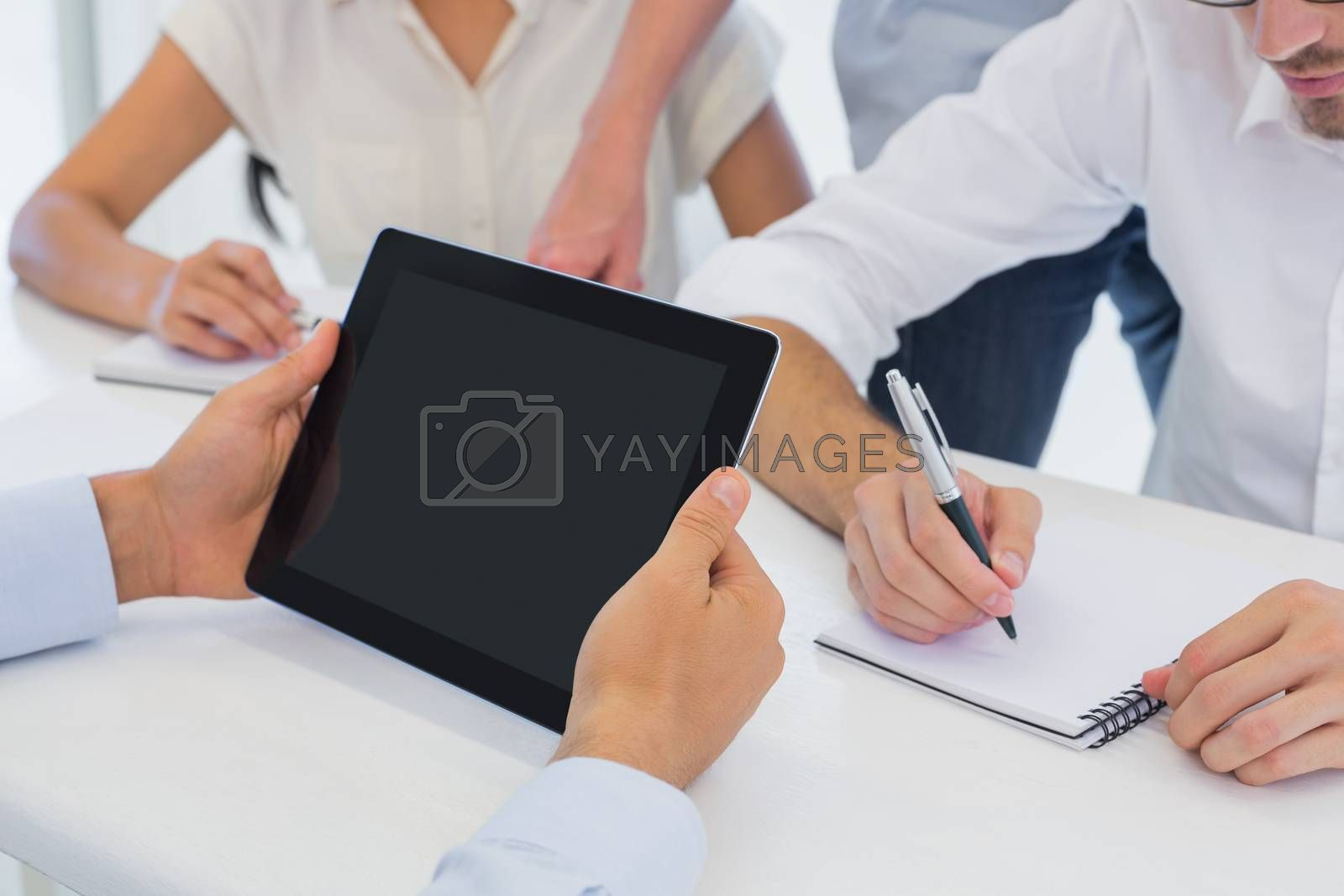 Royalty free image of Casual businessman using his tablet during meeting by Wavebreakmedia