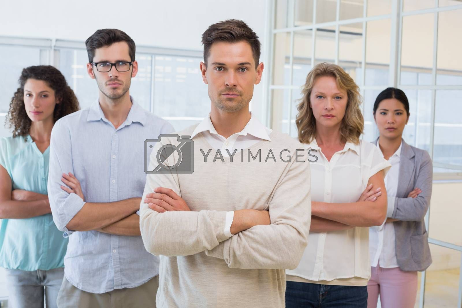 Royalty free image of Casual business team frowning at camera with arms crossed by Wavebreakmedia
