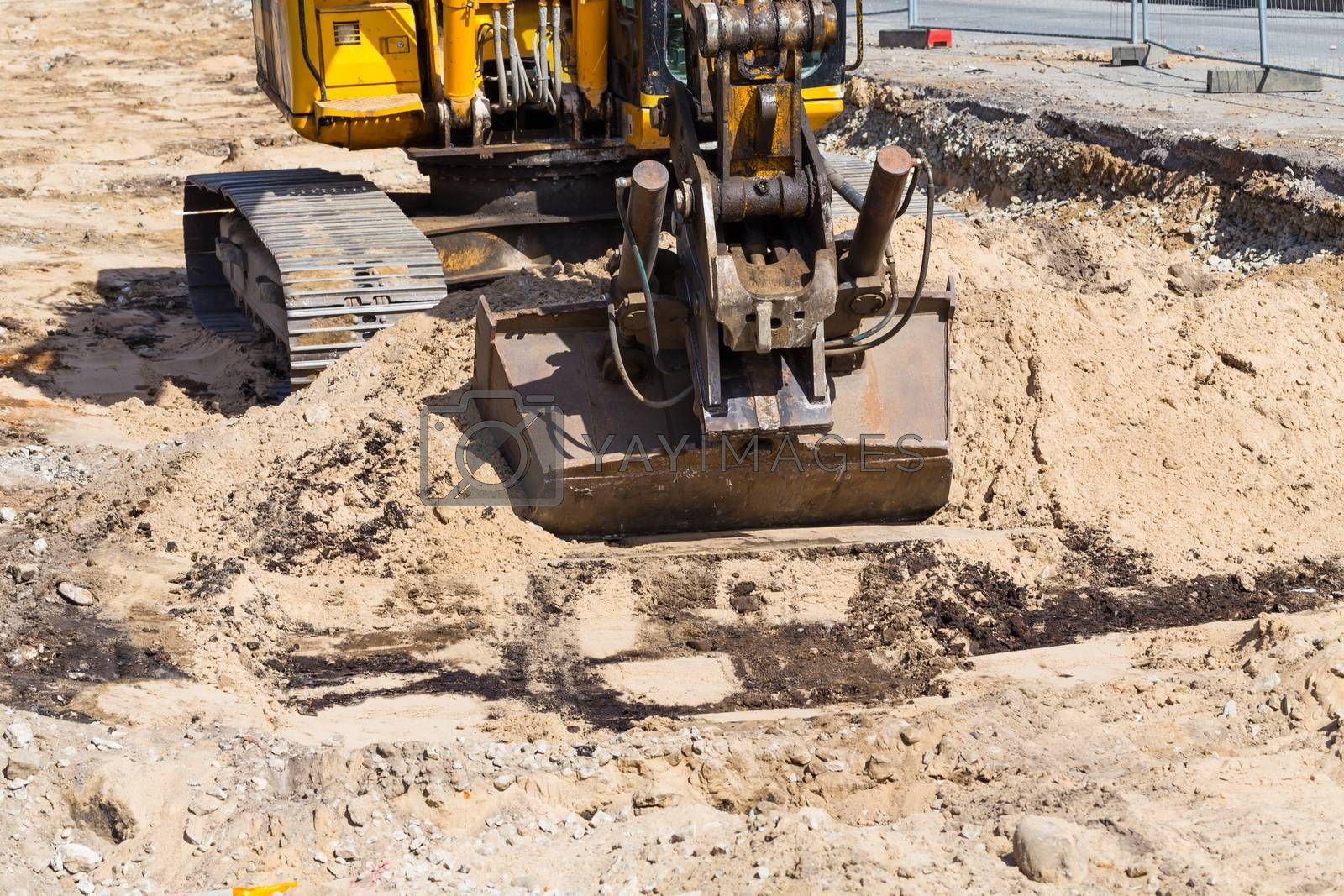 Royalty free image of heavy duty, industrial excavator moving soil and sand on road  by RTsubin