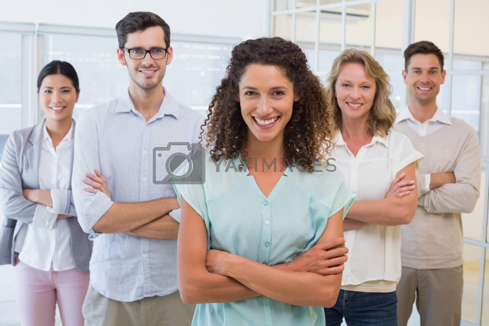 Royalty free image of Casual business team smiling at camera with arms crossed by Wavebreakmedia