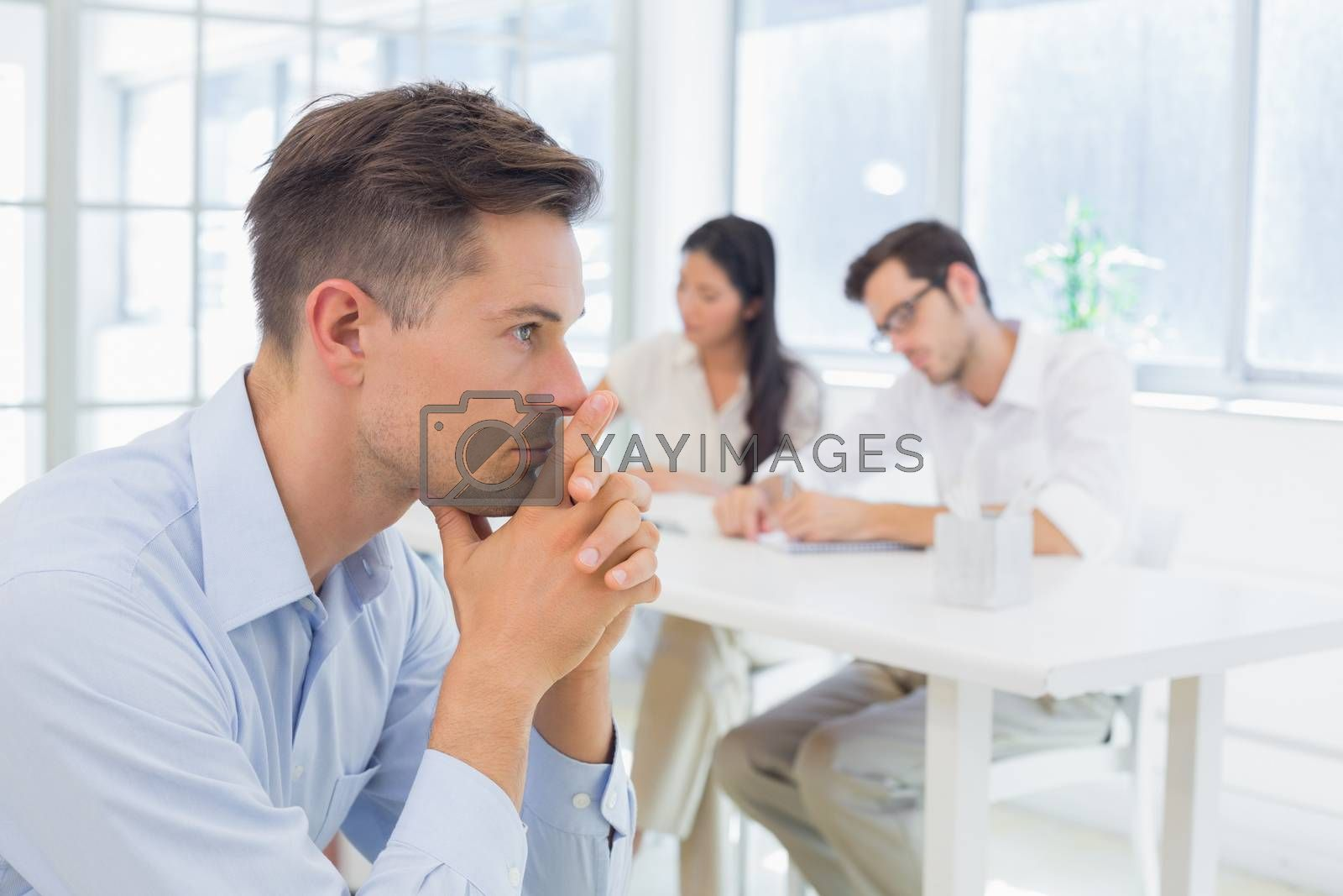 Royalty free image of Casual businessman thinking with team behind him by Wavebreakmedia