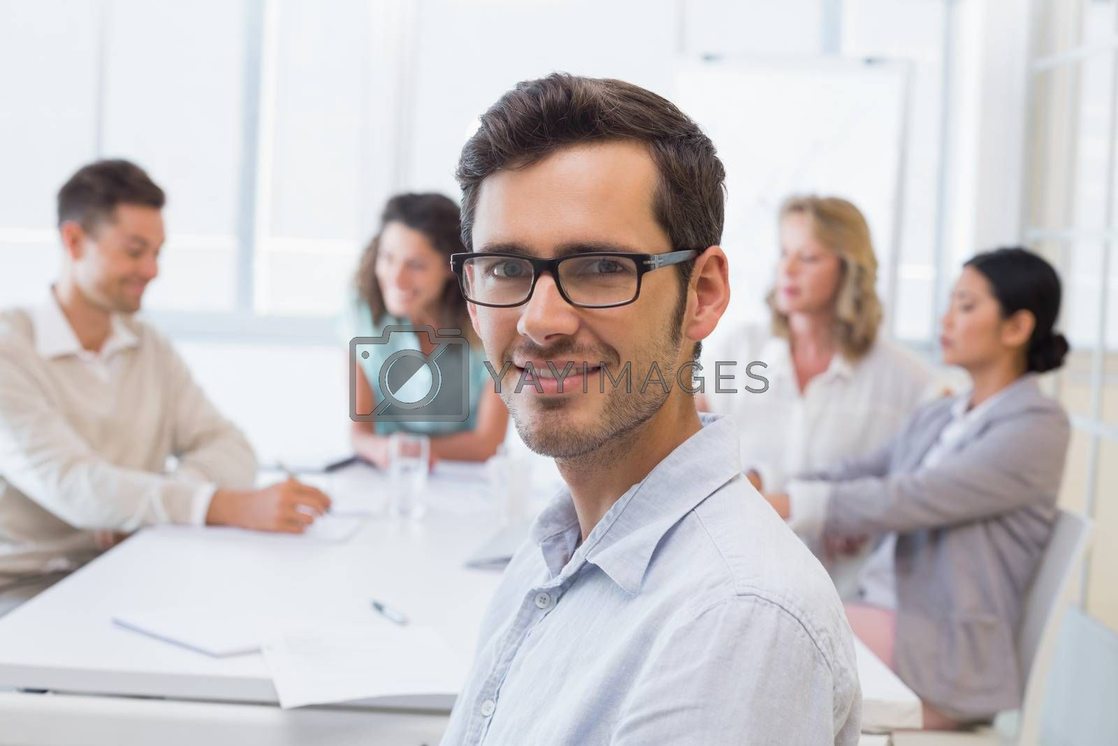 Royalty free image of Casual businessman smiling at camera during meeting by Wavebreakmedia