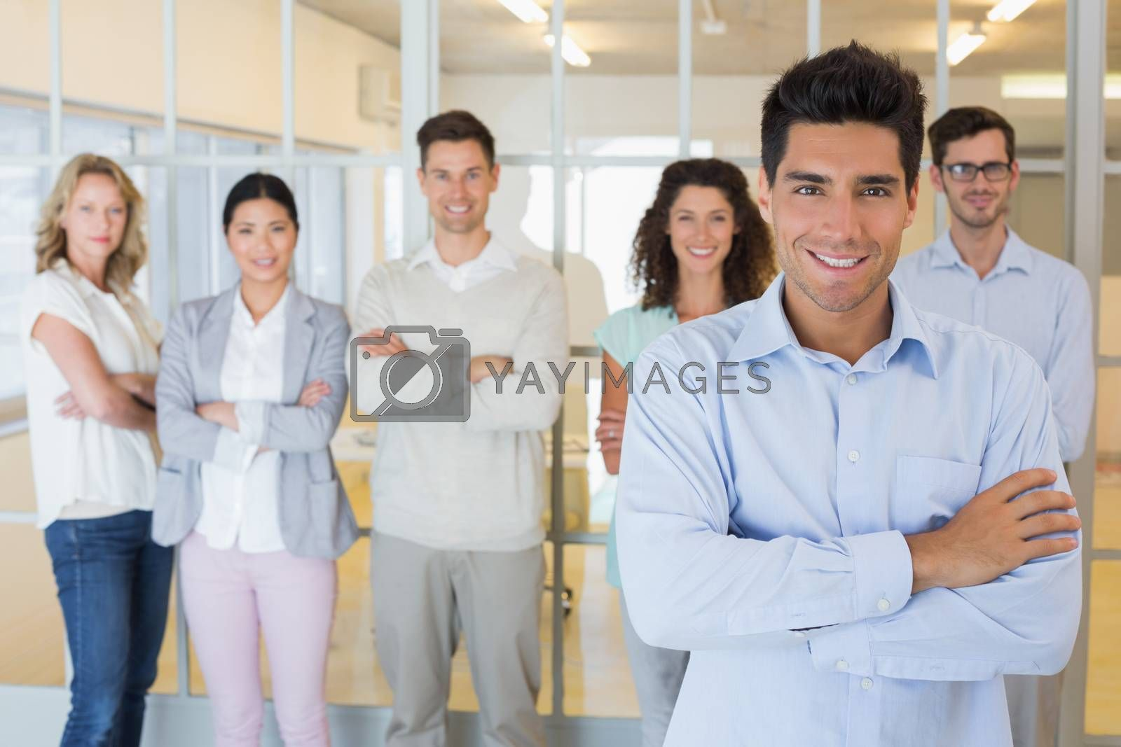 Royalty free image of Casual boss smiling at camera in front of business team by Wavebreakmedia