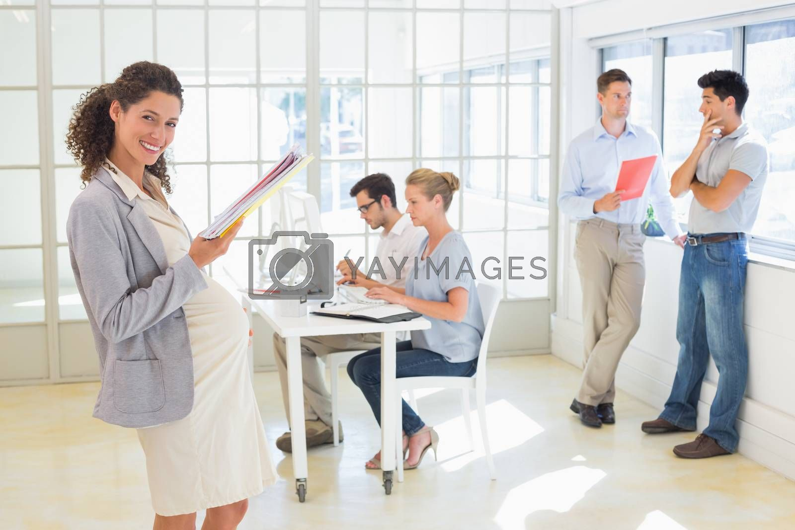 Royalty free image of Pregnant businesswoman smiling at camera with team behind her by Wavebreakmedia