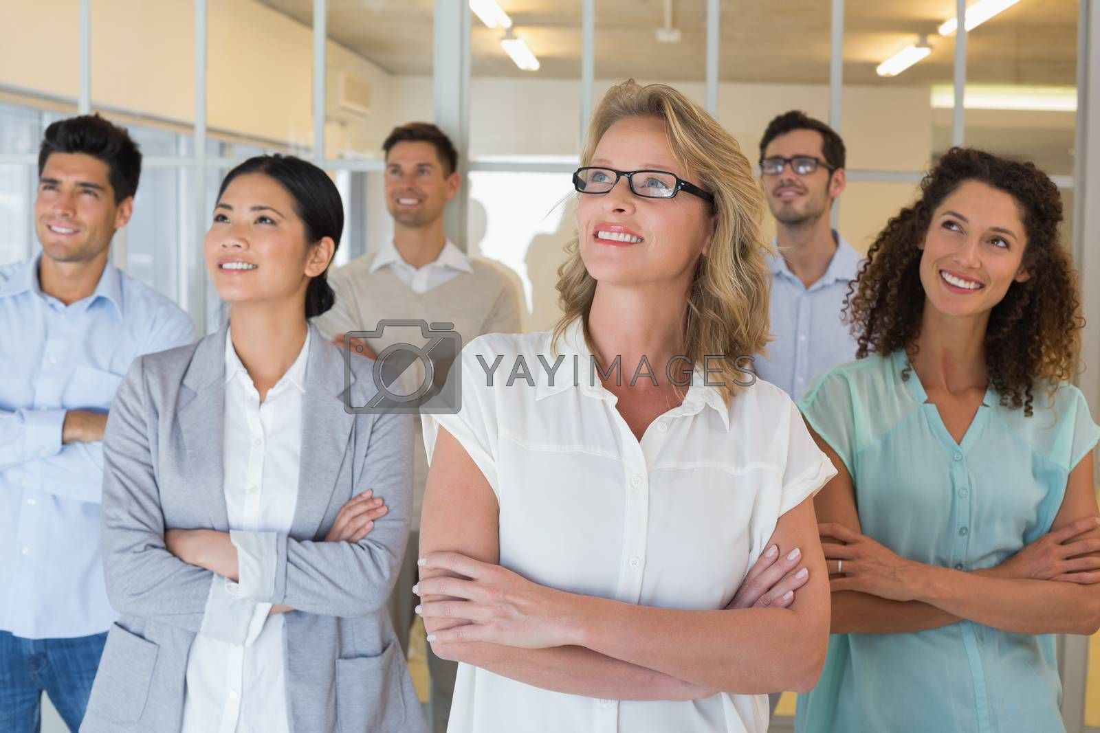 Royalty free image of Casual business team smiling with arms crossed looking up by Wavebreakmedia