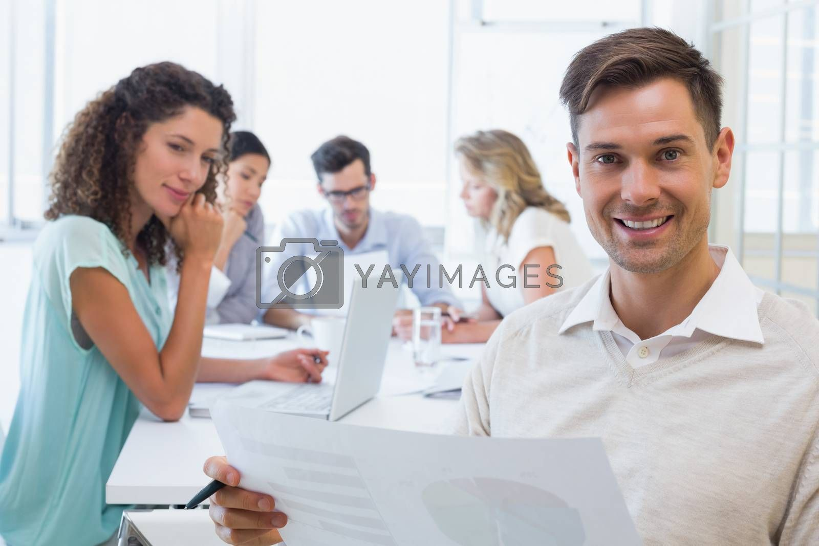 Royalty free image of Casual businessman reading document during meeting by Wavebreakmedia